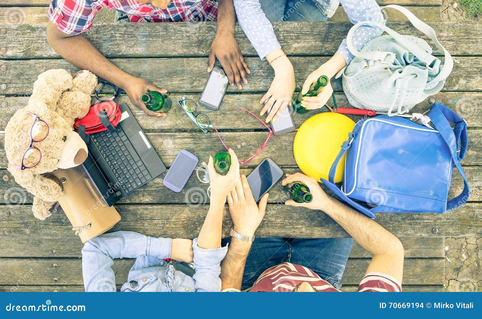 Группа в составе друзья выпивая пиво и используя передвижные умные телефоны