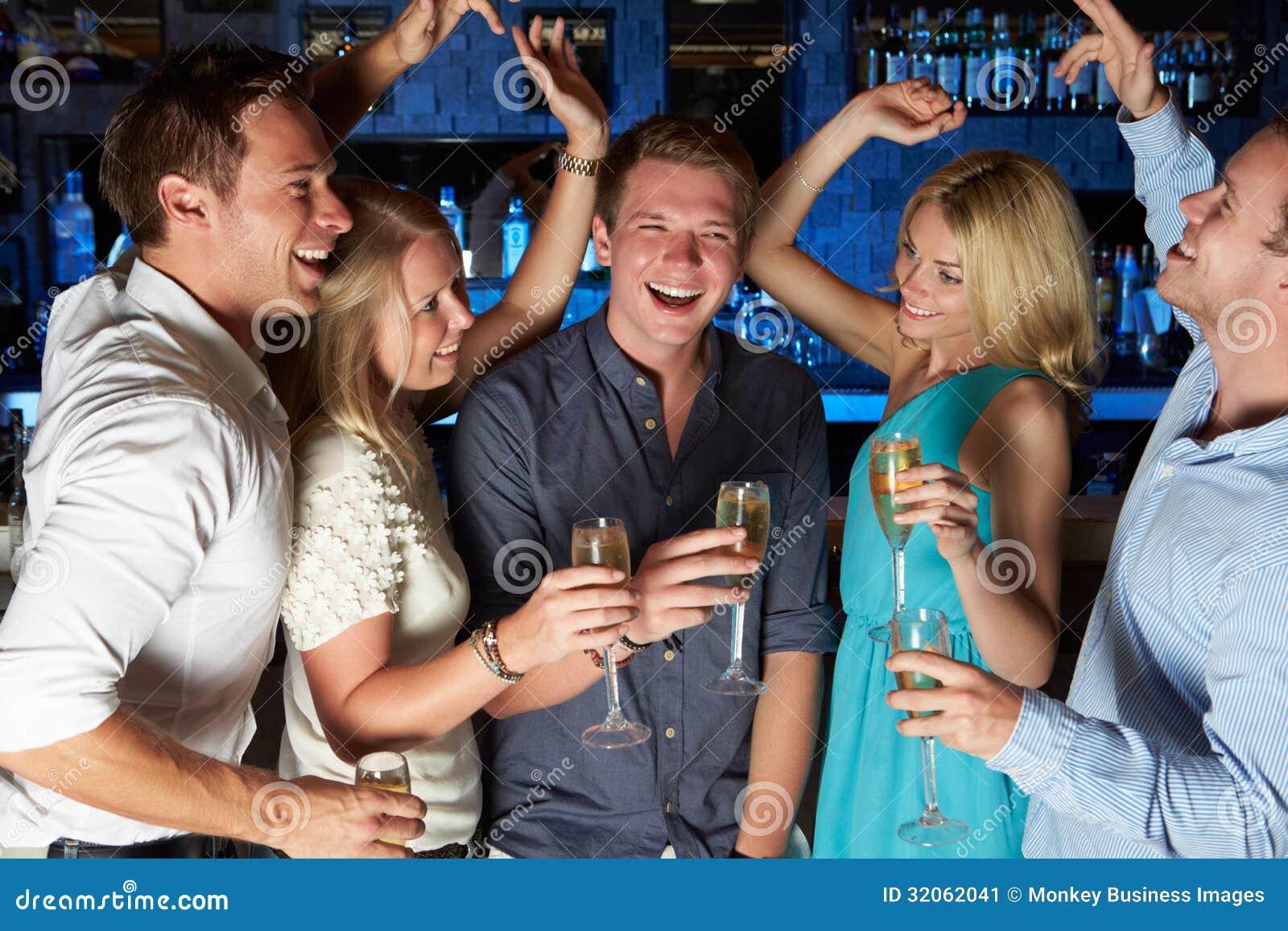 Группа в составе друзья наслаждаясь стеклом Шампани в баре