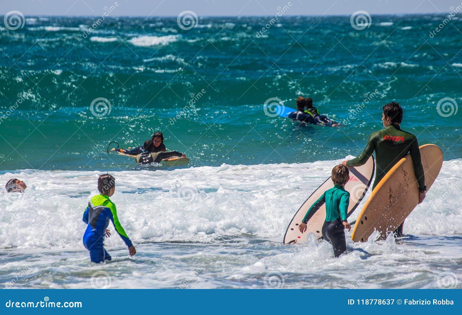 Группа в составе серферы на пляже на солнечный день, Португалии Cascais