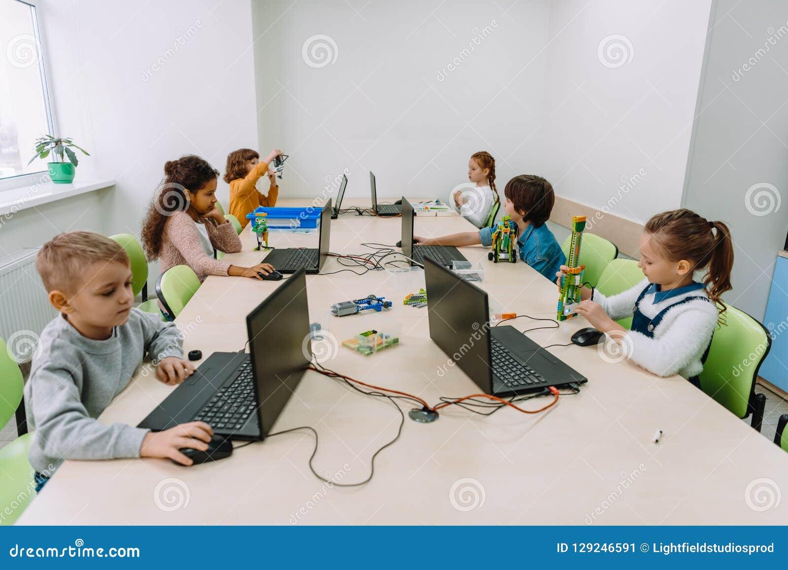 группа в составе сфокусированные дети работая с компьютерами