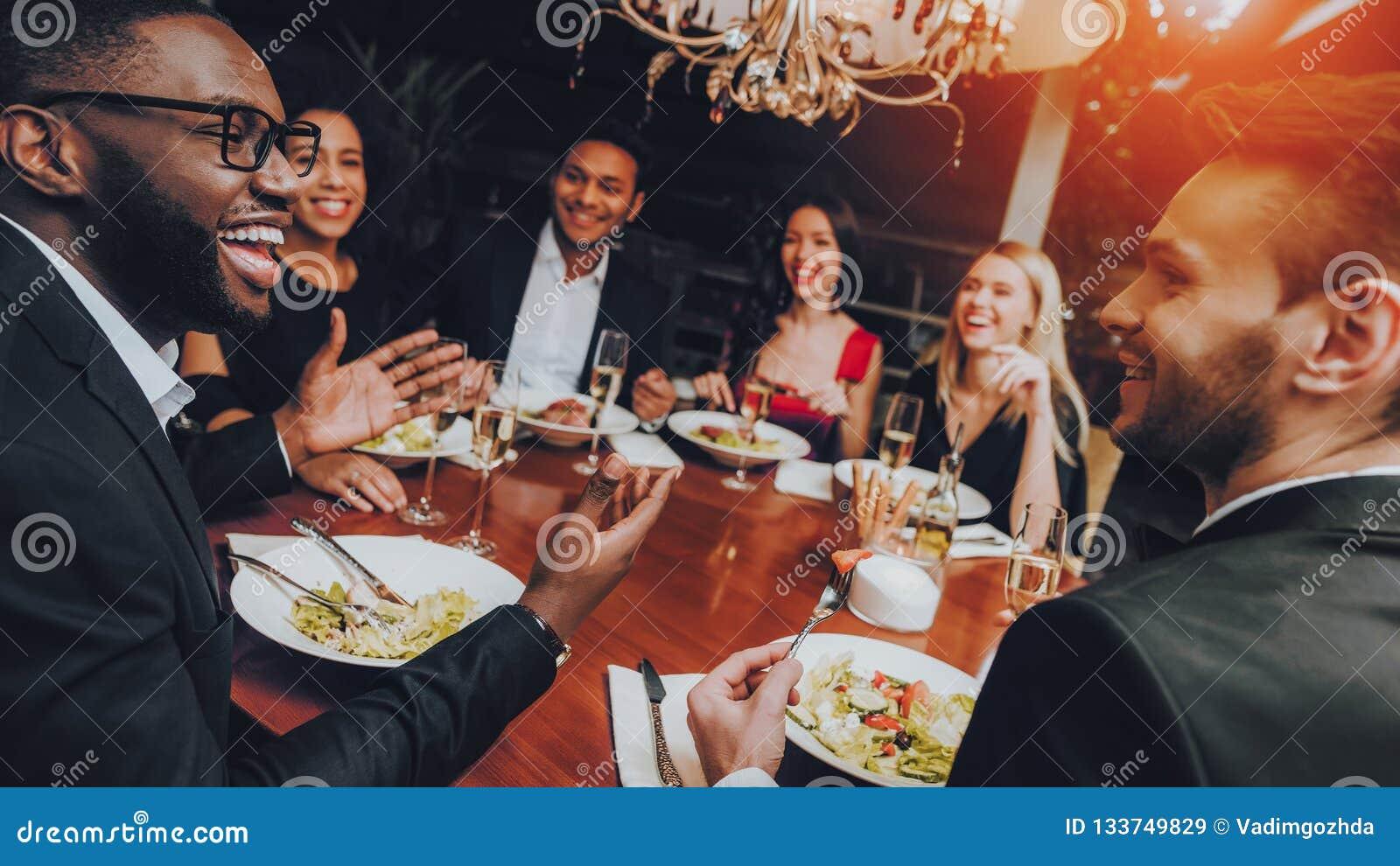 Группа в составе счастливые друзья встречая и имея обедающий