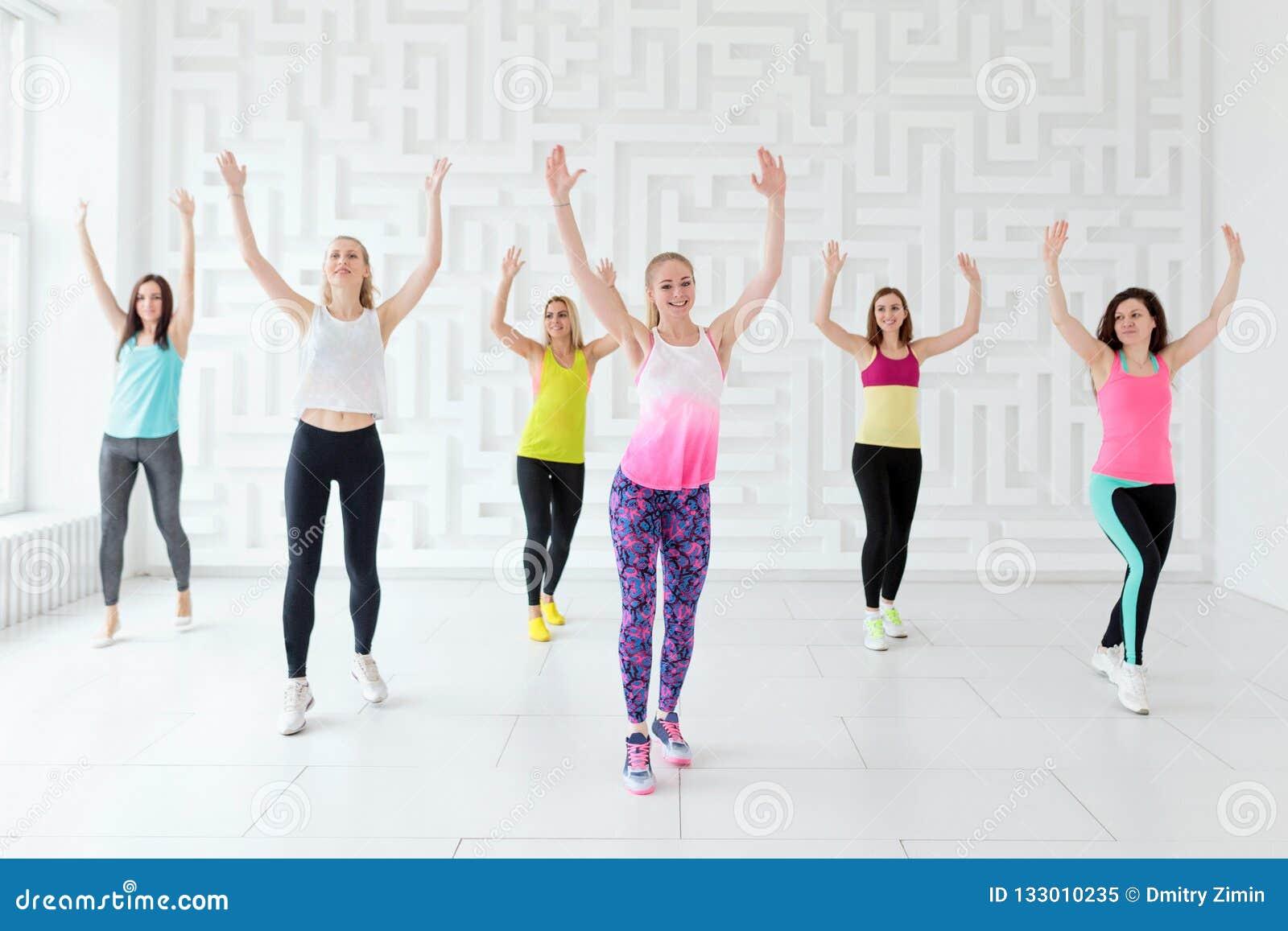 Группа в составе счастливые молодые женщины с тренером имея cardio разминку в студии фитнеса