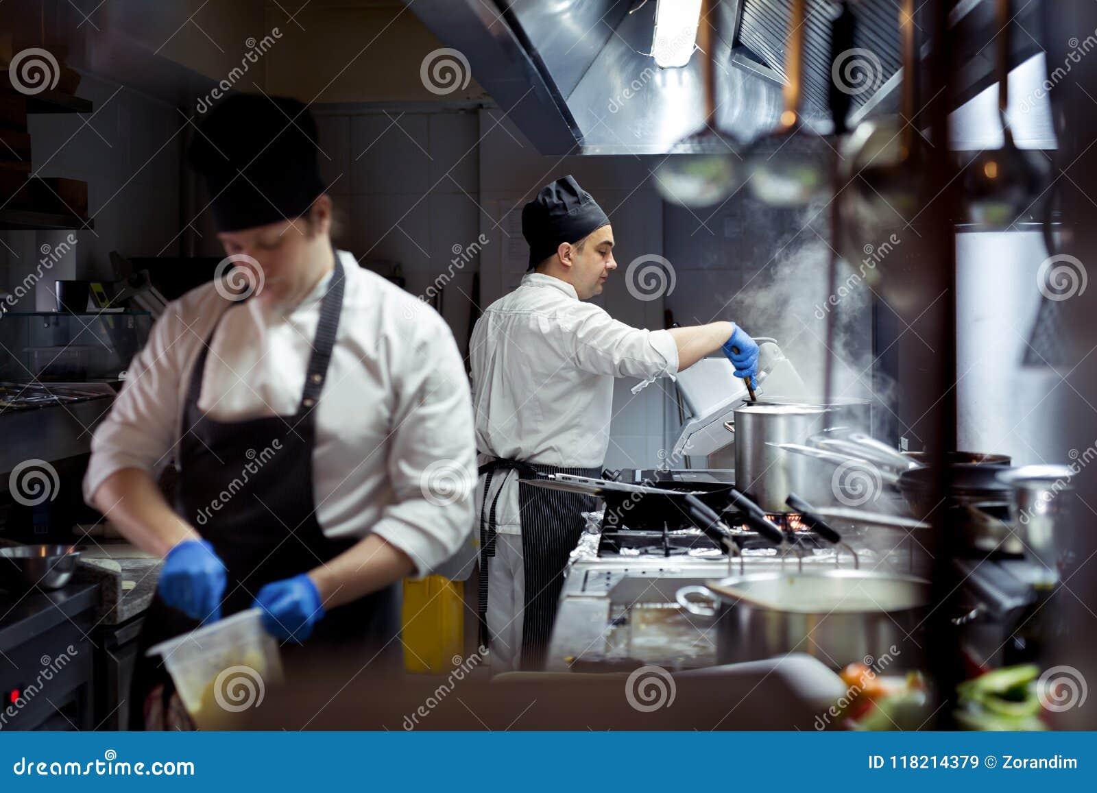 Группа в составе шеф-повар подготавливая еду в кухне ресторана