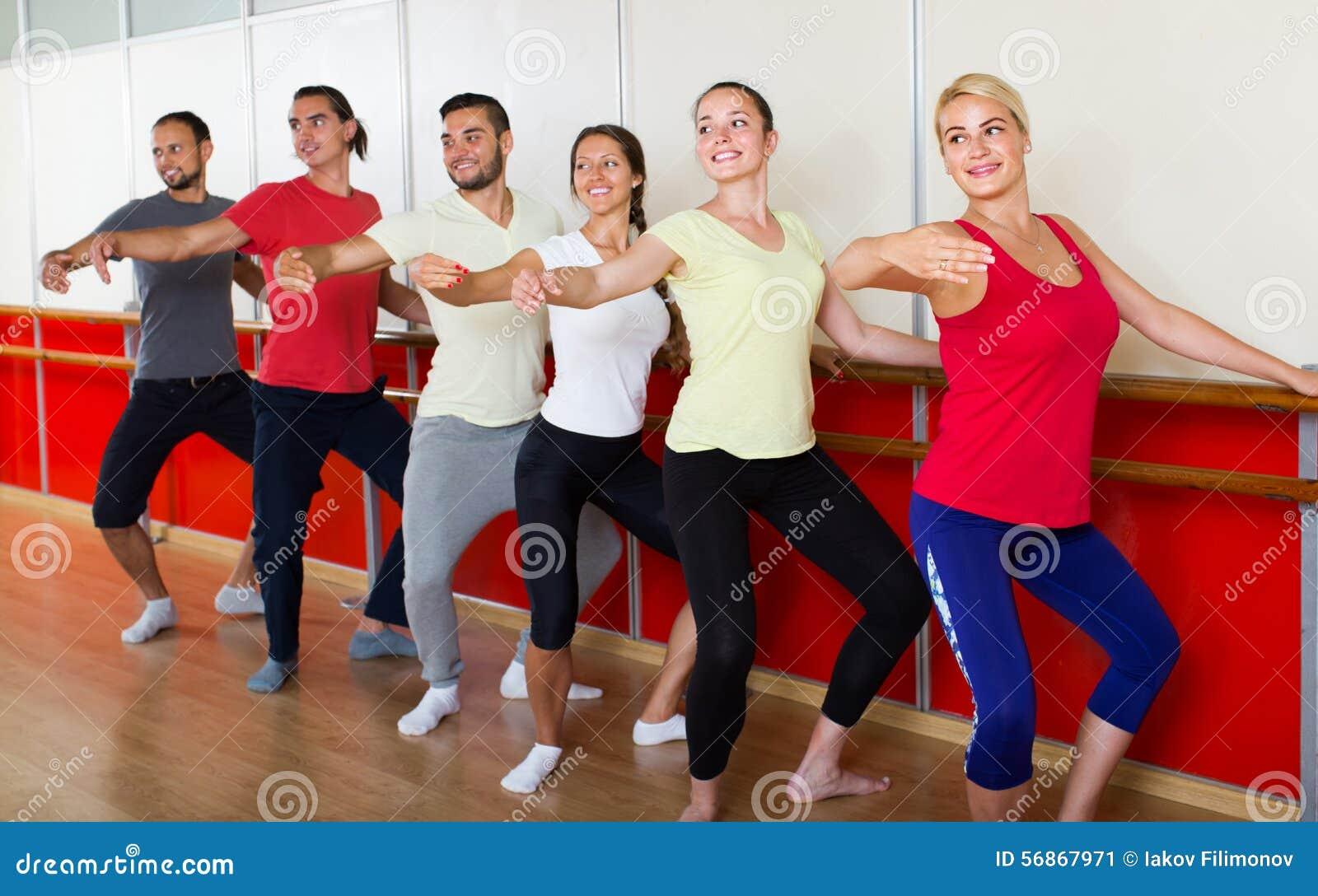 Группа в составе люди и женщины практикуя на barre балета