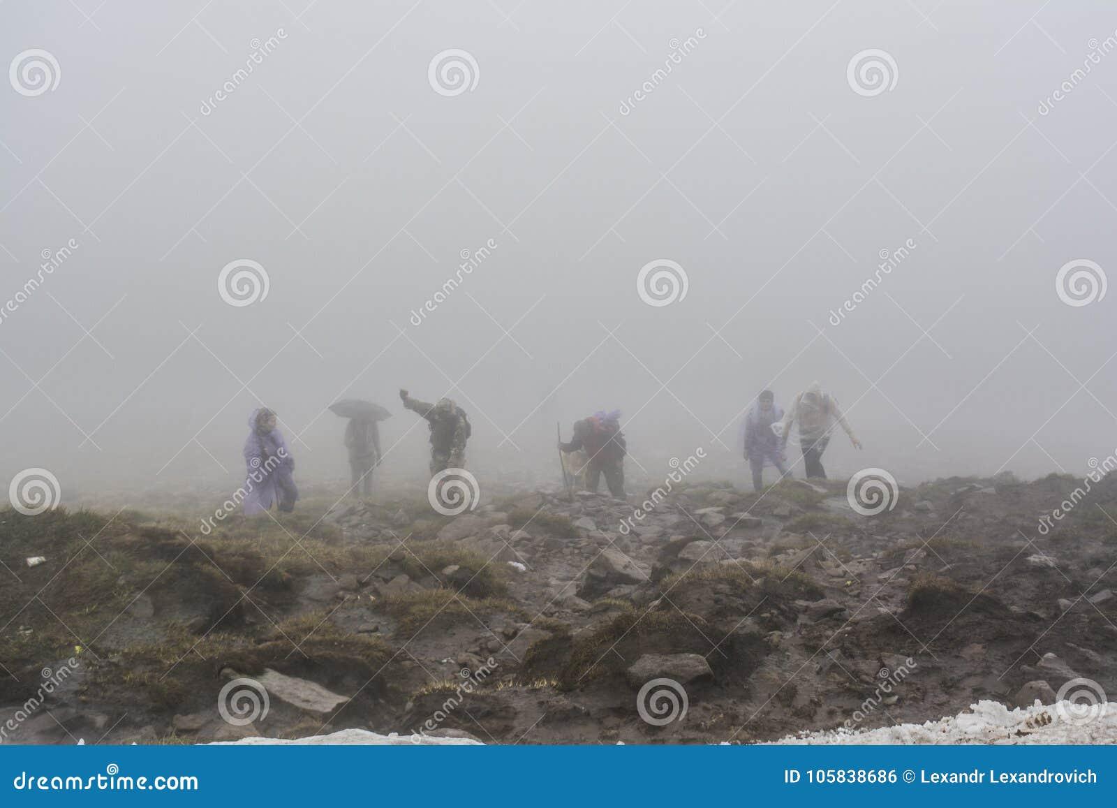Группа в составе alpinists взбираясь вверх на верхней части горы