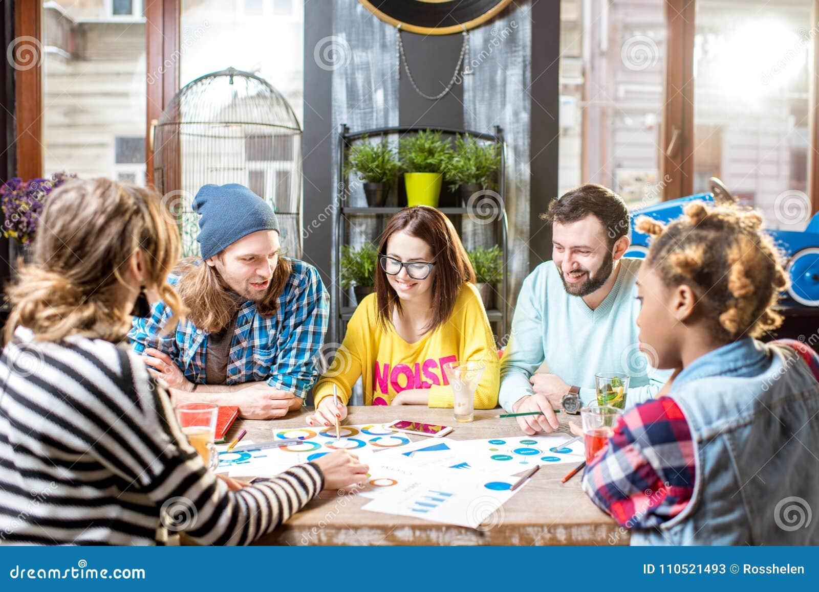 Группа людей работая совместно в кафе