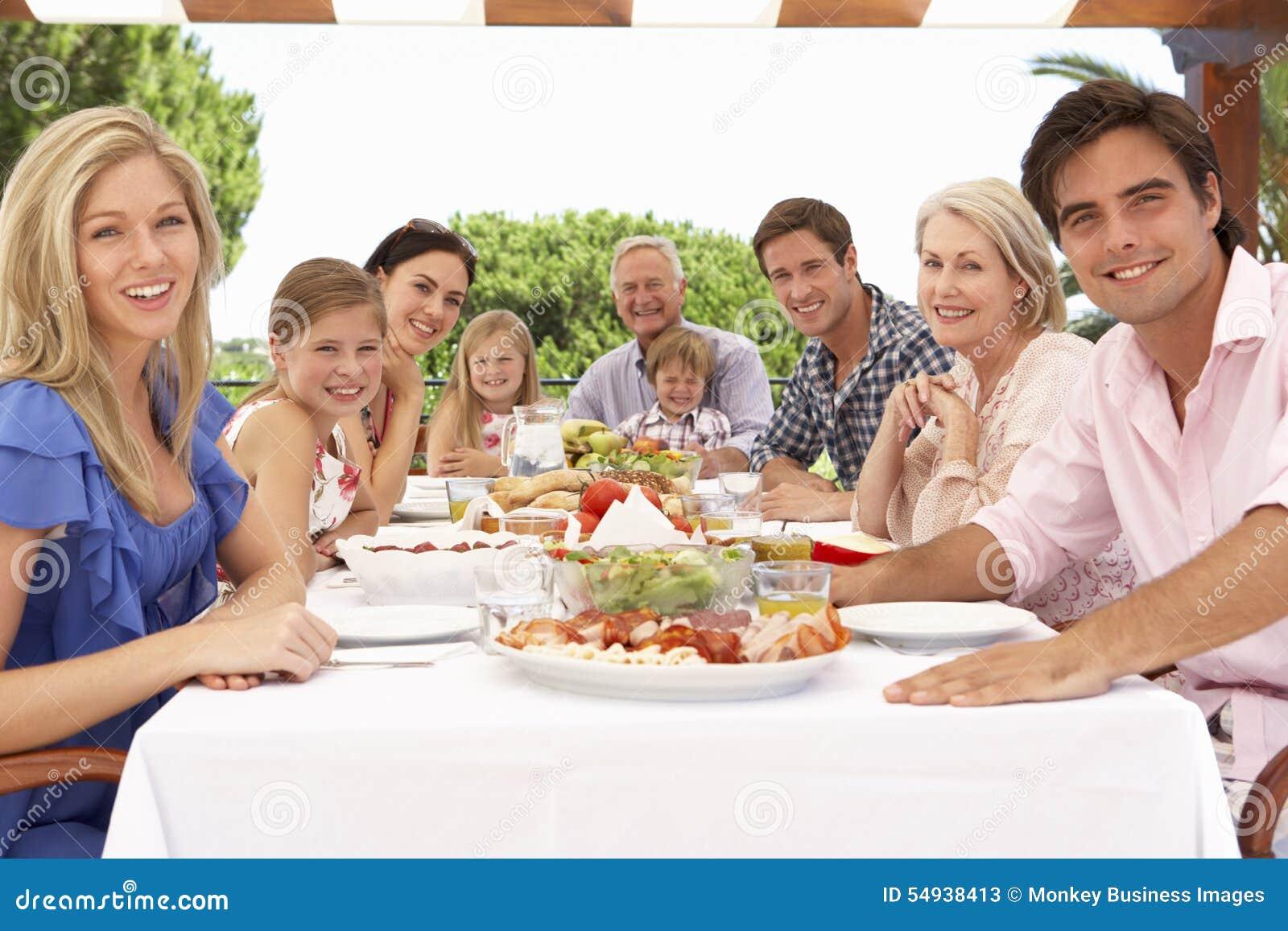 Группа семьи из нескольких поколений наслаждаясь внешней едой совместно