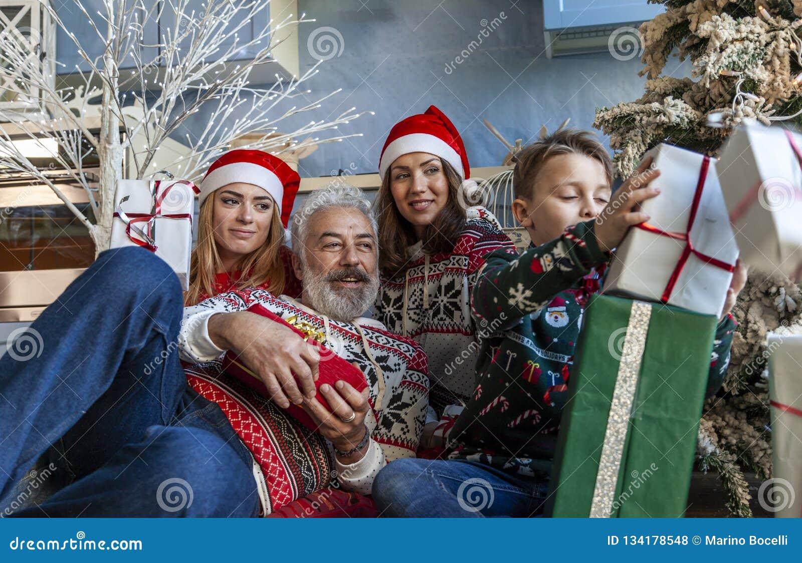 Группа семьи под полночью рождественской елки ждать
