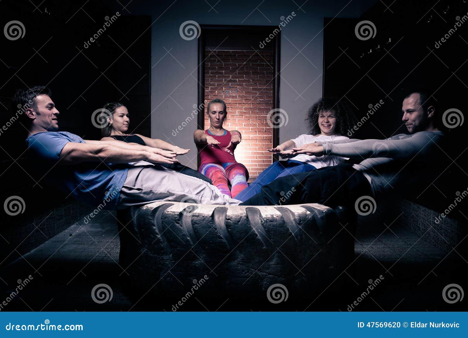 Группа фитнеса делать нажимает поднимает Малый делать группы людей нажим-поднимает на автошине Молодые спортсмены разрабатывая