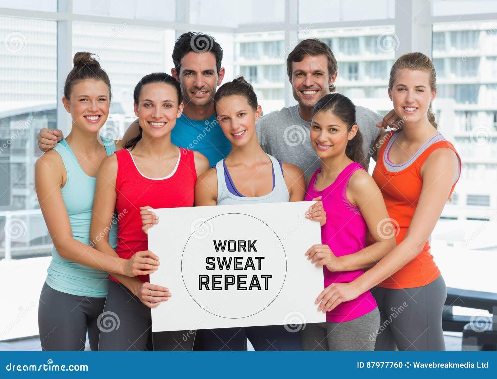 Группа людей держа карточку с работой, потом и повторением текста перед окном в спортзале