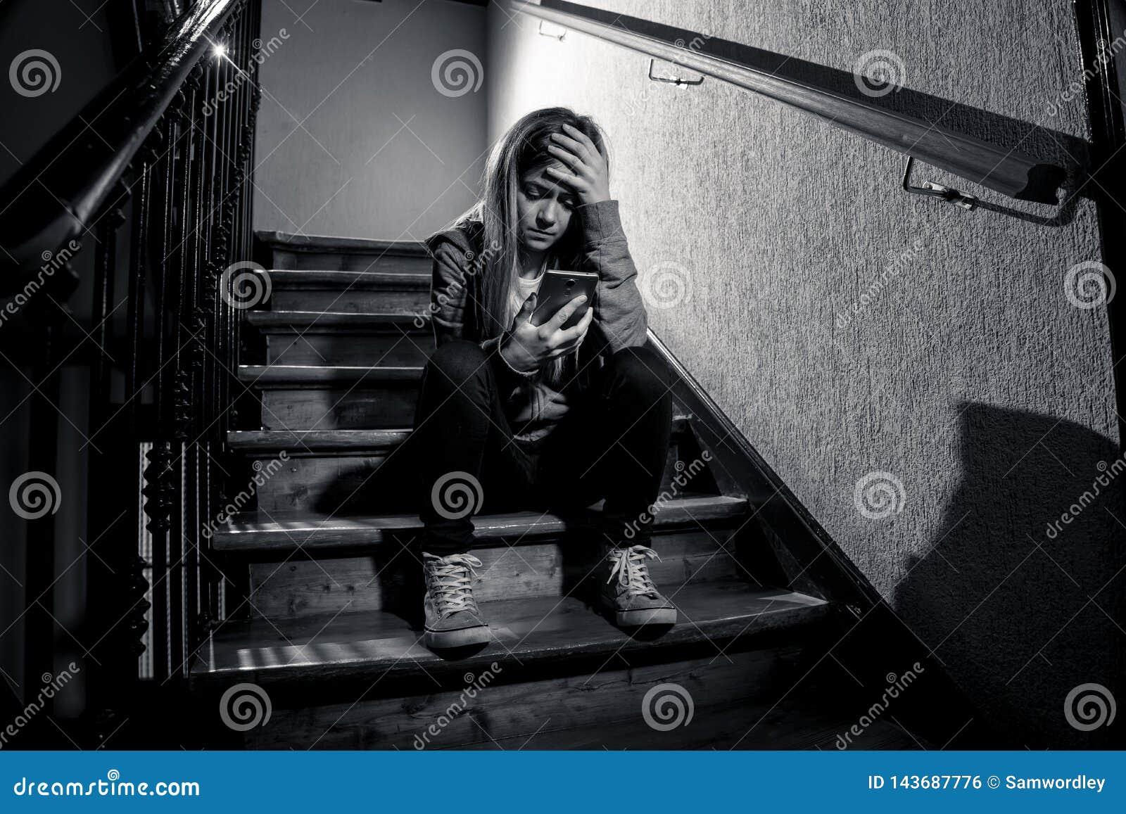 Грустная подавленная несчастная девушка подростка страдая от cyberbullying мобильным умным телефоном сидя самостоятельно