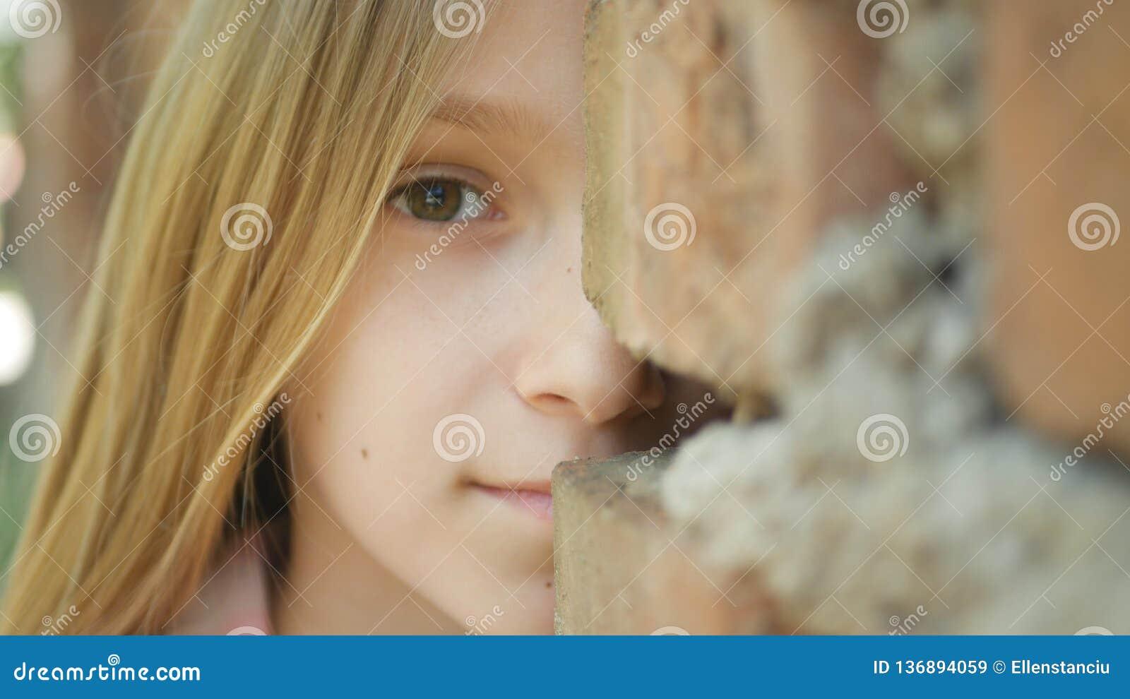 Грустная сторона ребенка играя прятк, вспугнутую девушку за стенами усмехаясь в камере