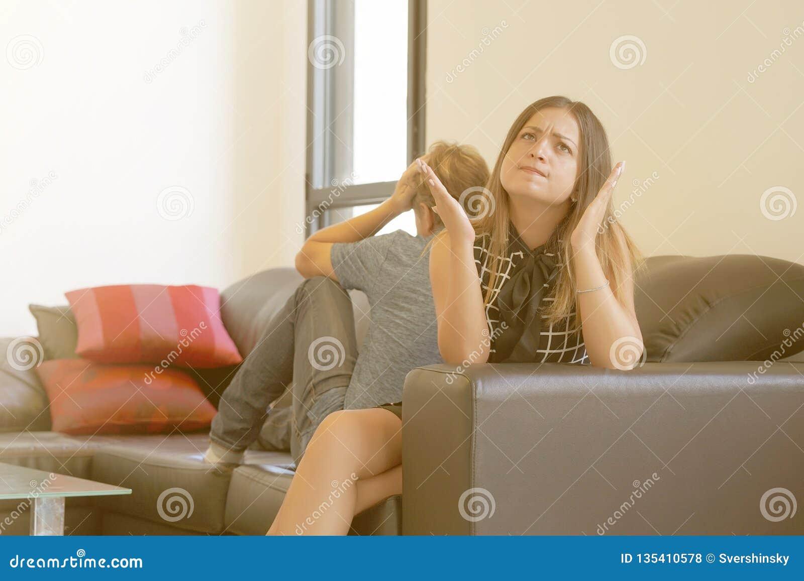 Грустные пары после аргумента или распад сидя на софе в живущей комнате в доме крытом