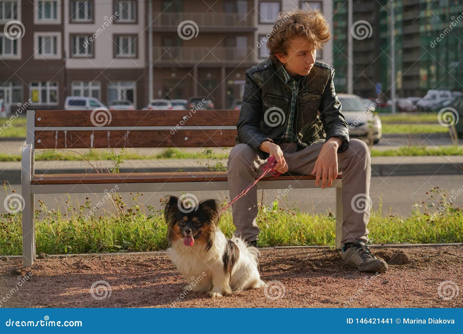 Грустный сиротливый парень сидя на стенде с его собакой затруднения отрочества в концепции связи