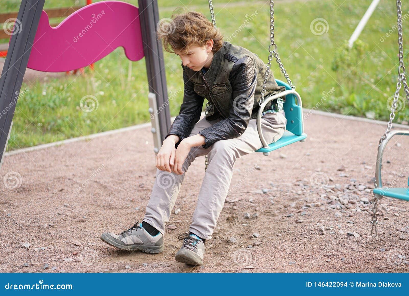 Грустный сиротливый подросток на открытом воздухе на спортивной площадке затруднения отрочества в концепции связи