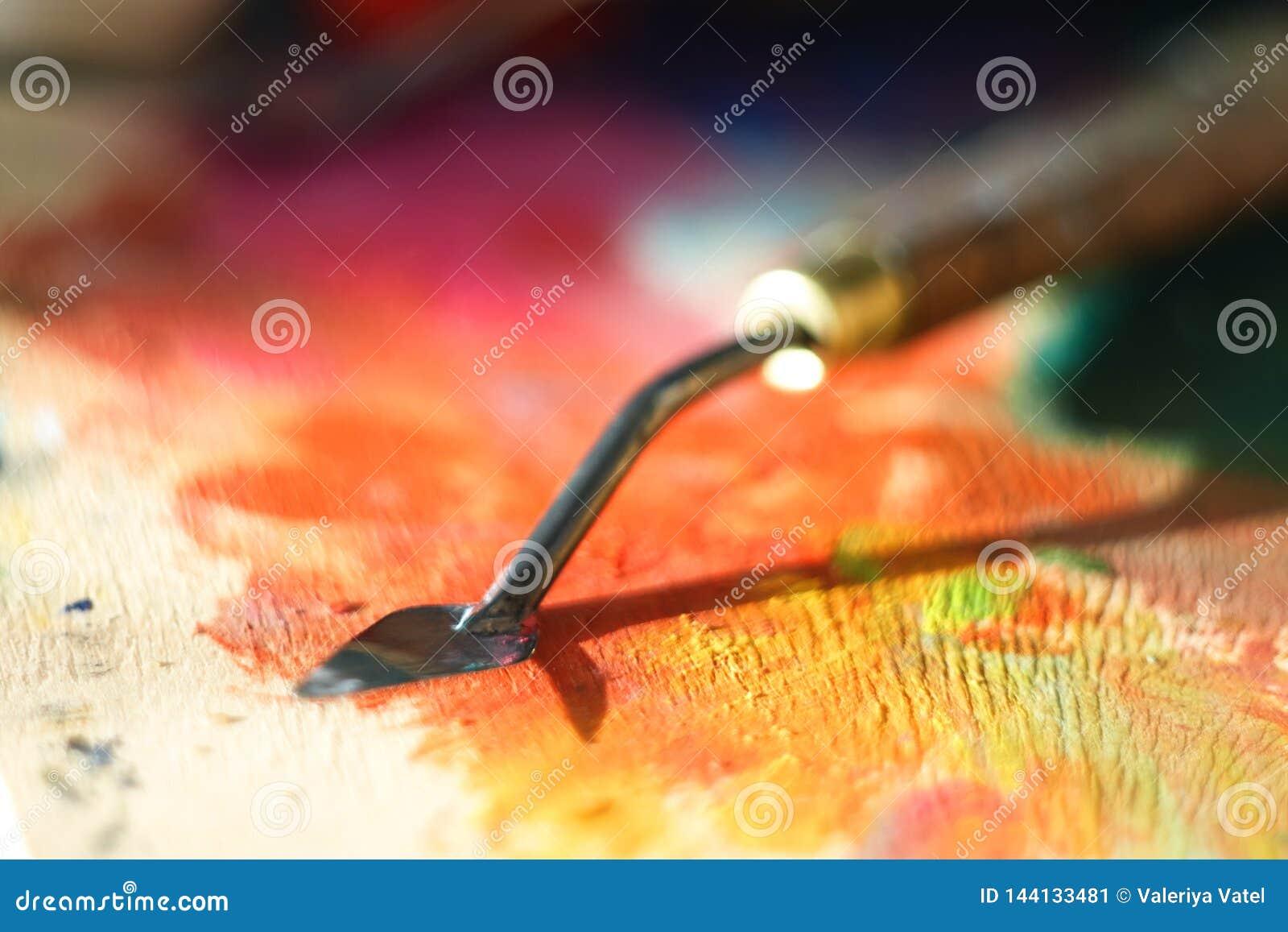 Грязный нож палитры после работы на крася лож на деревянной палитре