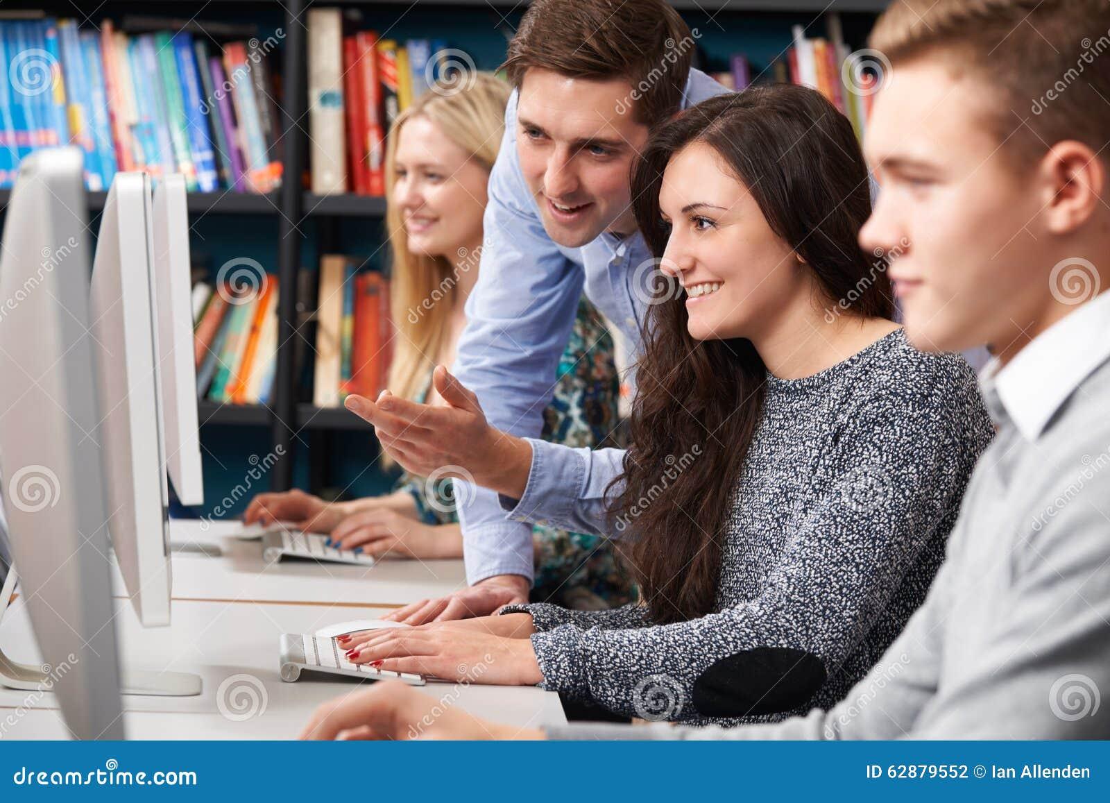 Гувернер помогая подростковым студентам работая на компьютерах