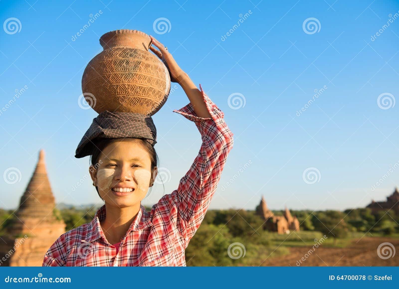 Глиняный горшок нося азиатского традиционного женского фермера на голове