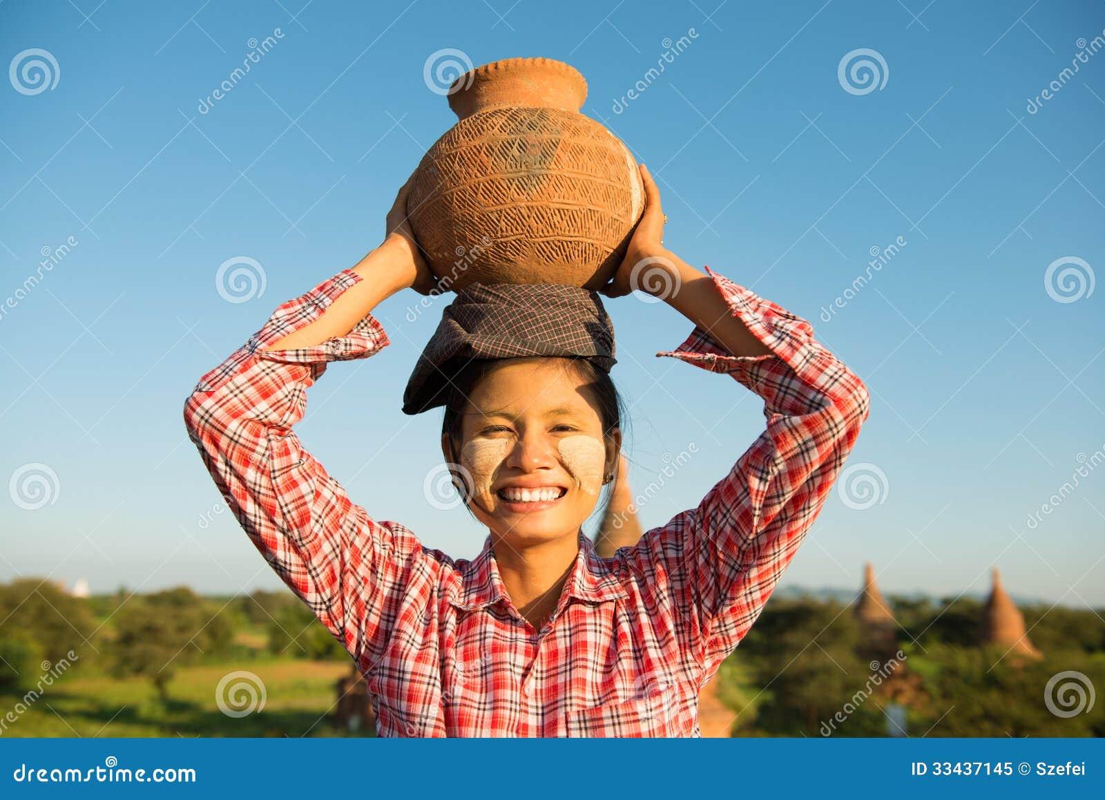 Глиняный горшок нося азиатского традиционного женского фермера