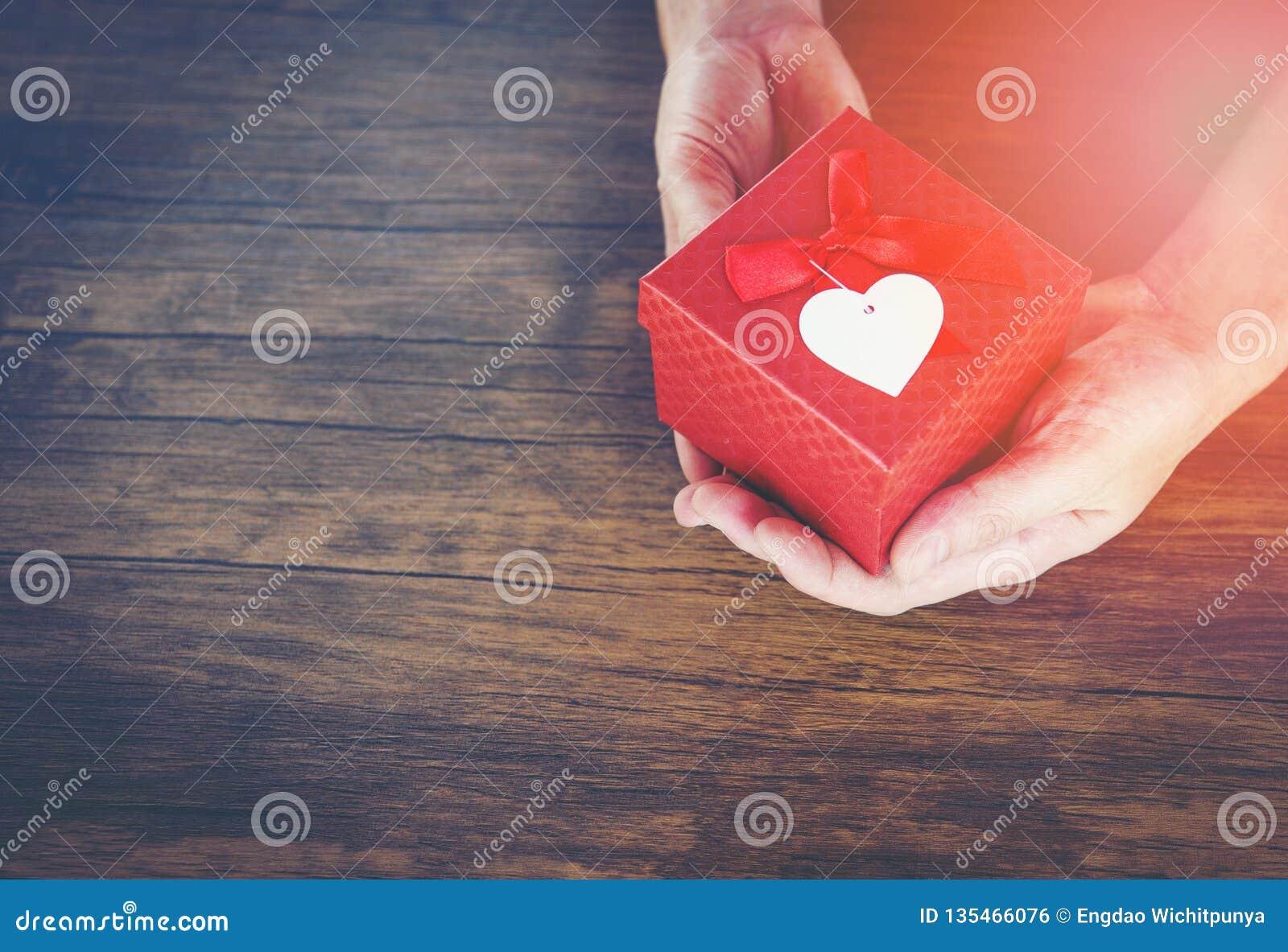 Дайте человека любов держа небольшую красную присутствующую коробку в руках с сердцем на день Святого Валентина любов давая подар