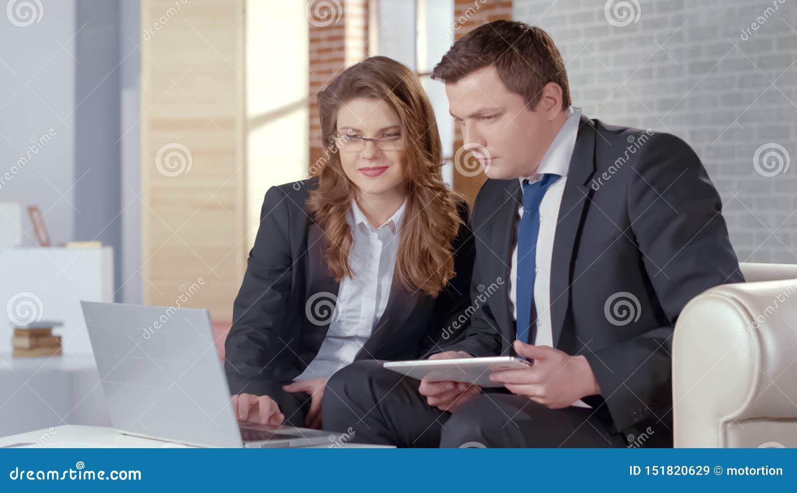 Дама и человек дела проверяя представление на ноутбуке, сотрудничают в деле