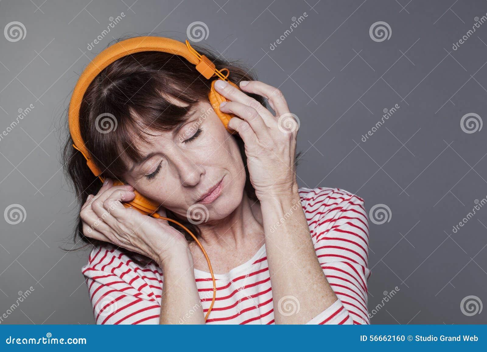 Дама постаретая серединой peacfully наслаждаясь музыкой