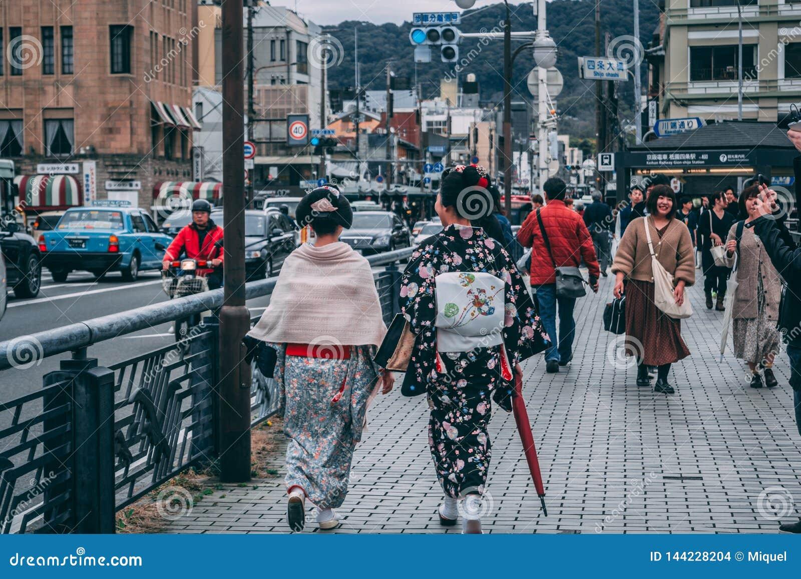 Дамы в традиционных японских обмундированиях идя улицы Киото