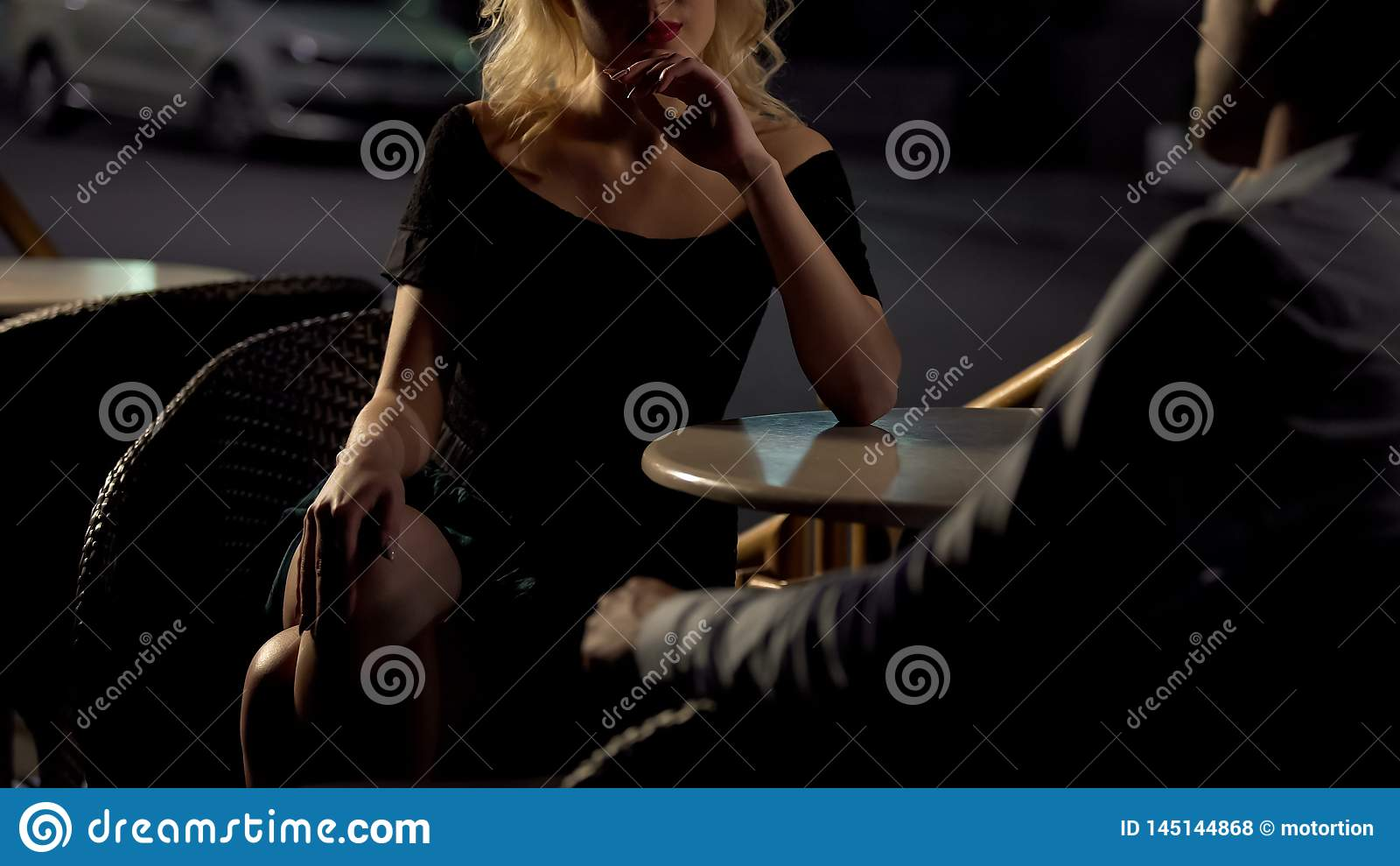 Дата вечера, красивое женское усаживание в кафе и сокращая человек, ст