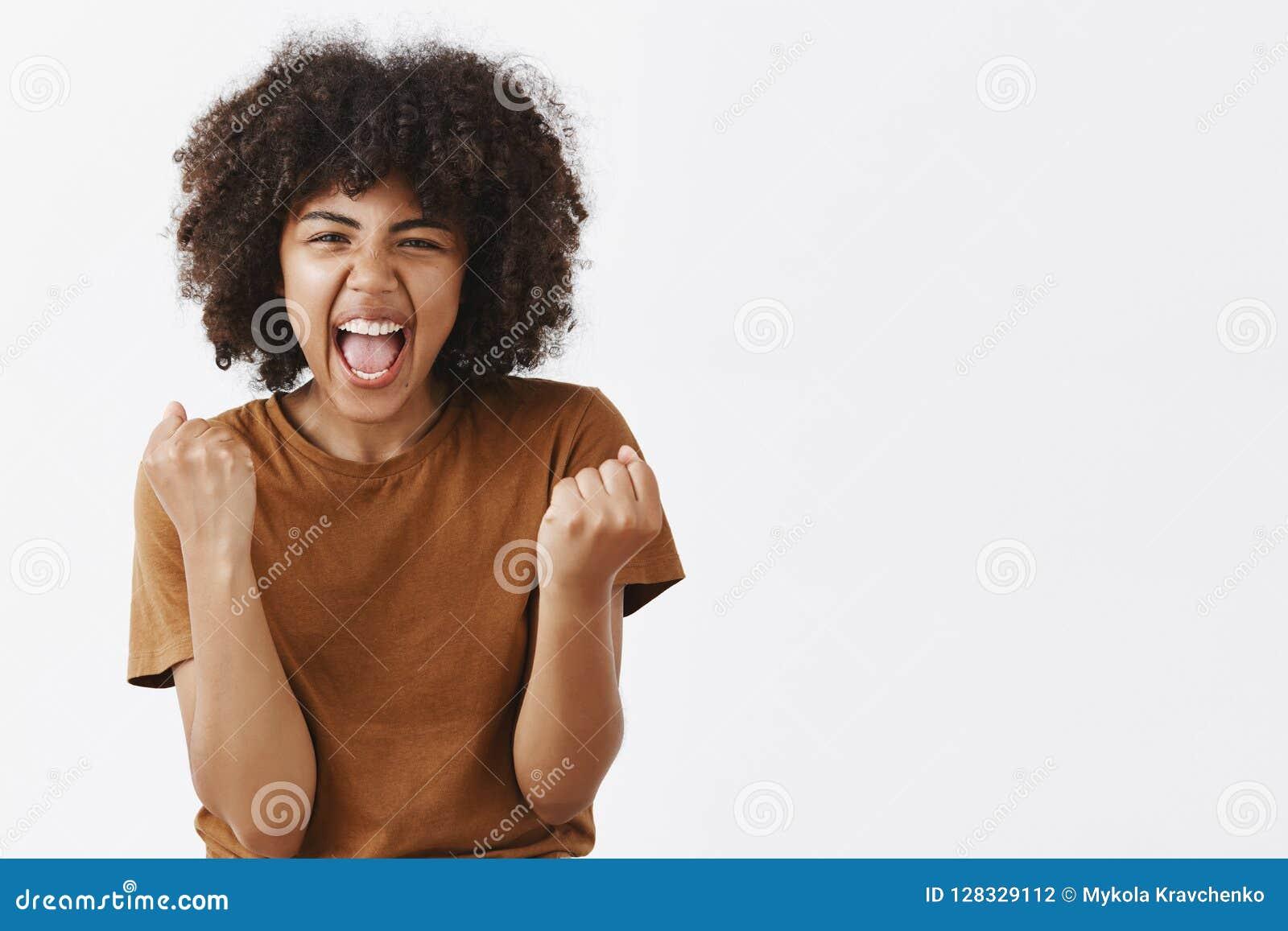 Да мы сделали его команда Портрет радостной excited и эмотивной счастливой темнокожей студентки веселя для любимой команды