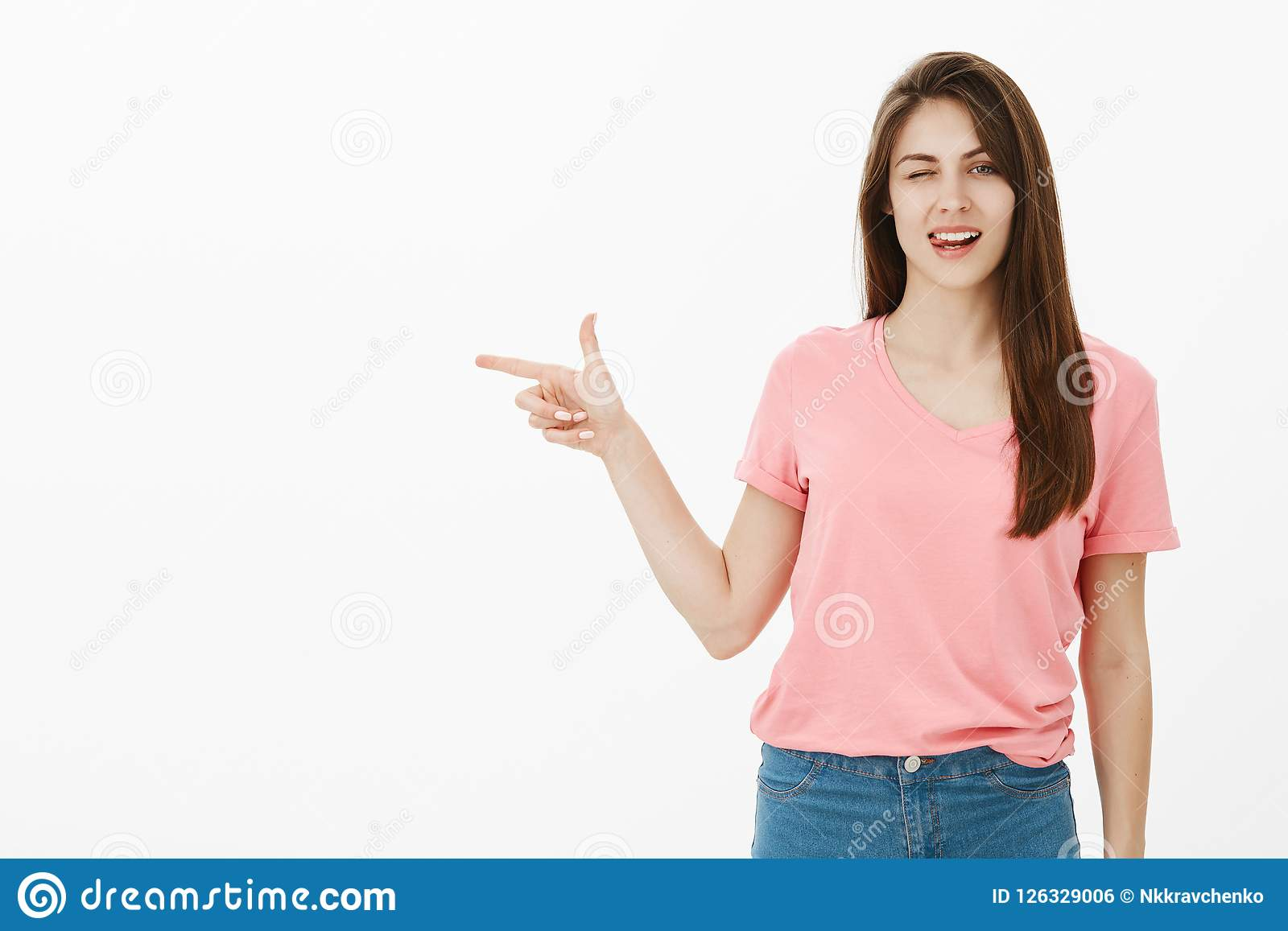 Да, оно определенно что нам нужно Милая flirty молодая женщина в розовой футболке, gazing sensually и подмигивая, показывая