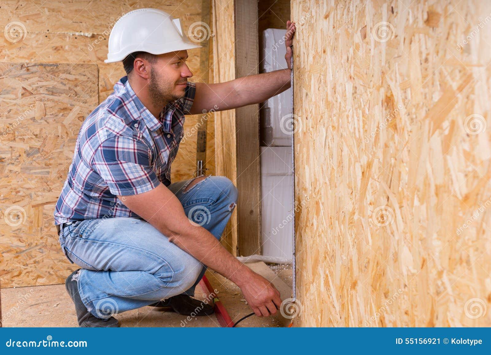 Дверная рама построителя измеряя в незаконченном доме