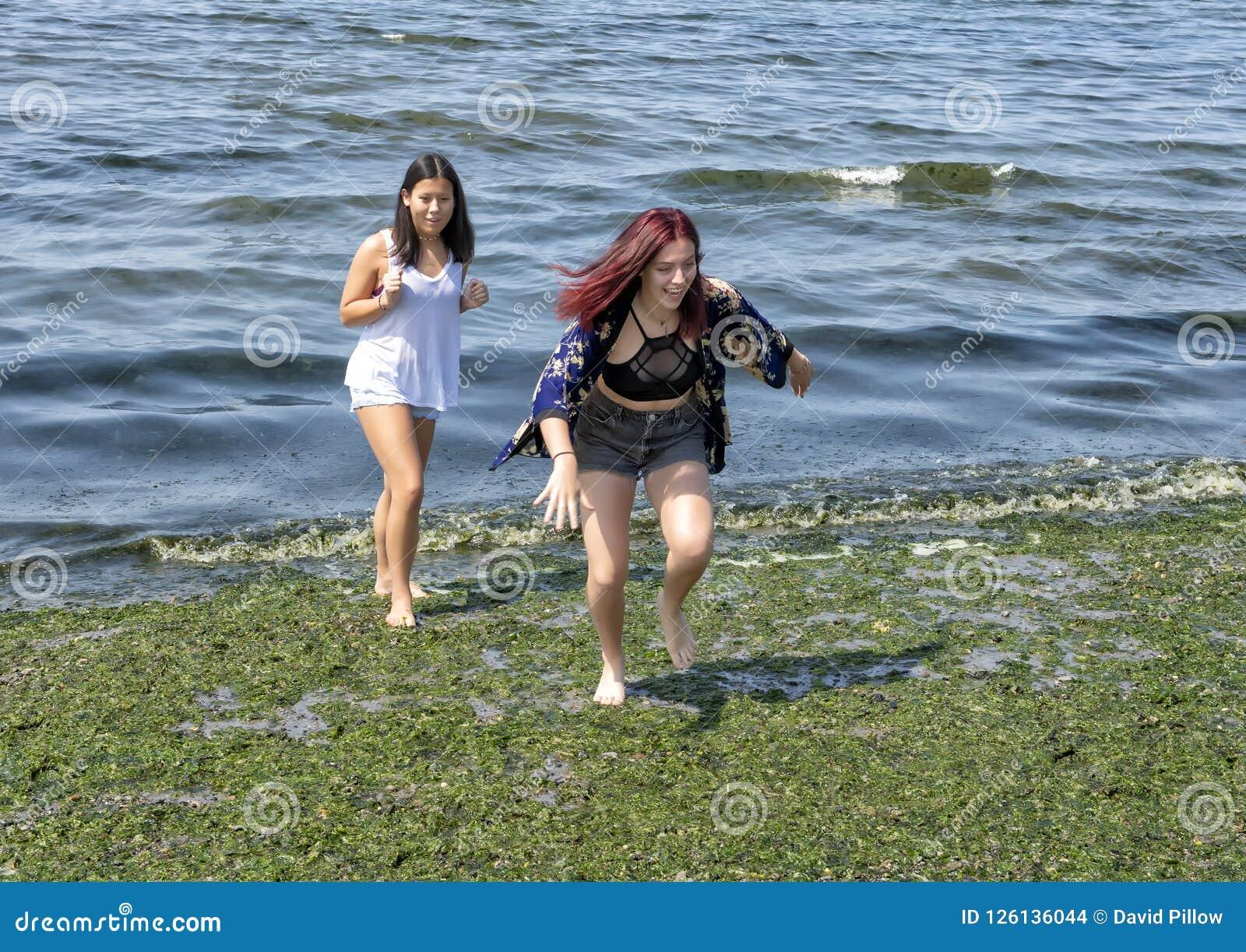 Девочка-подросток бежать от воды на шламе предусматривал пляж Alki пока ее вахты кузена с занятностью
