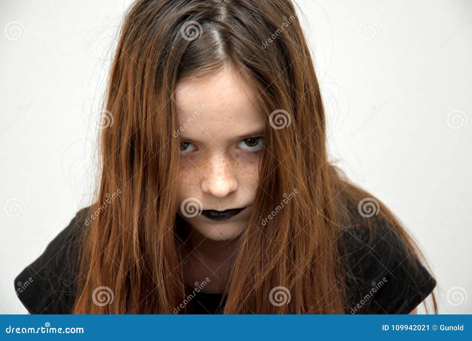 Девочка-подросток в готическом стиле смотря очень сердитый