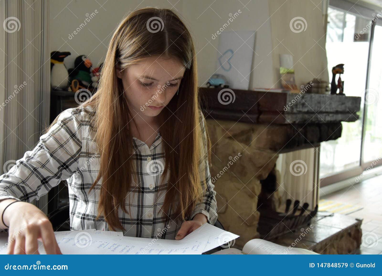 Девочка-подросток делая ее домашнюю работу математик