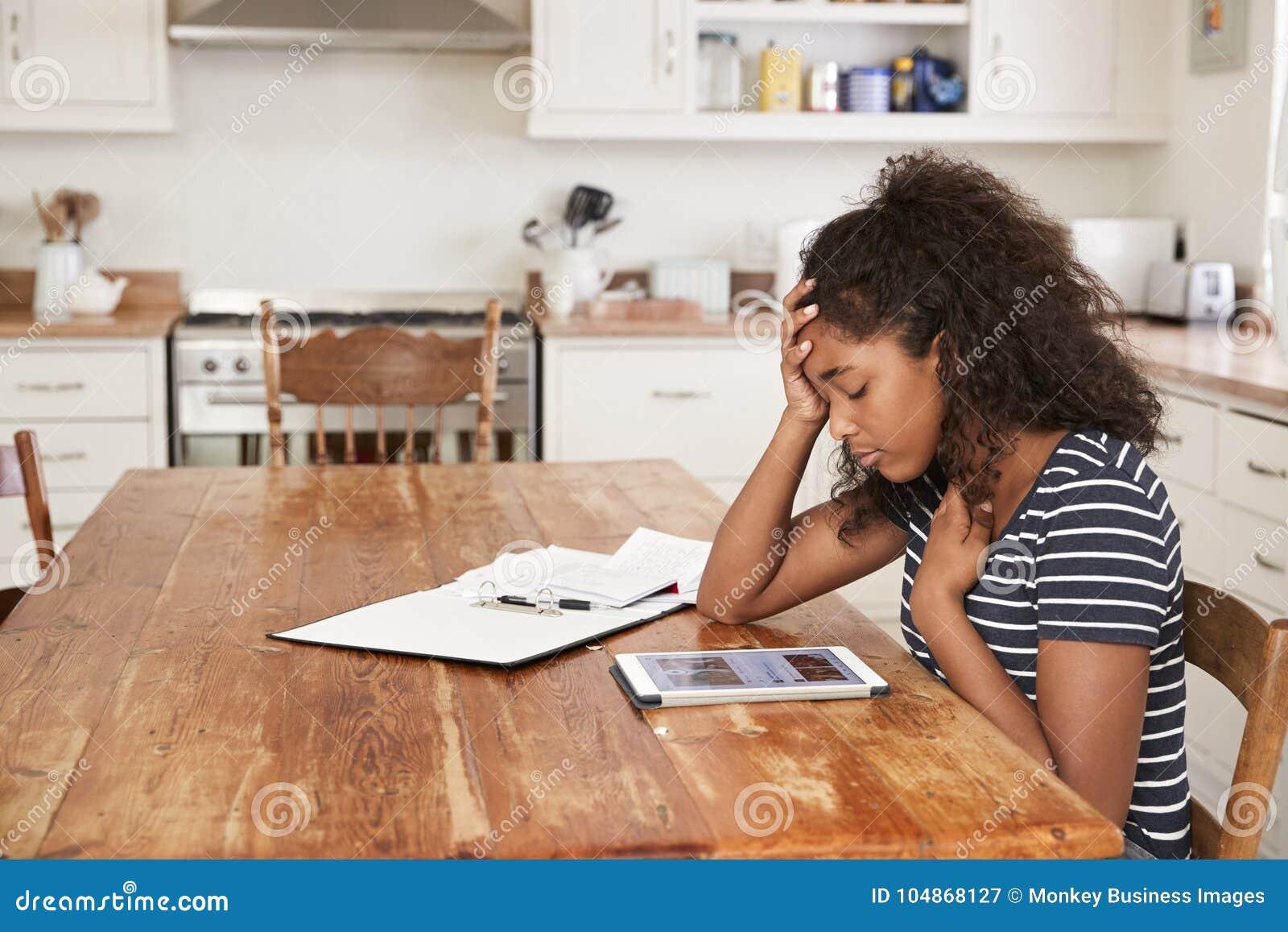 Девочка-подросток дома используя таблетку цифров будучи задиранным на линии