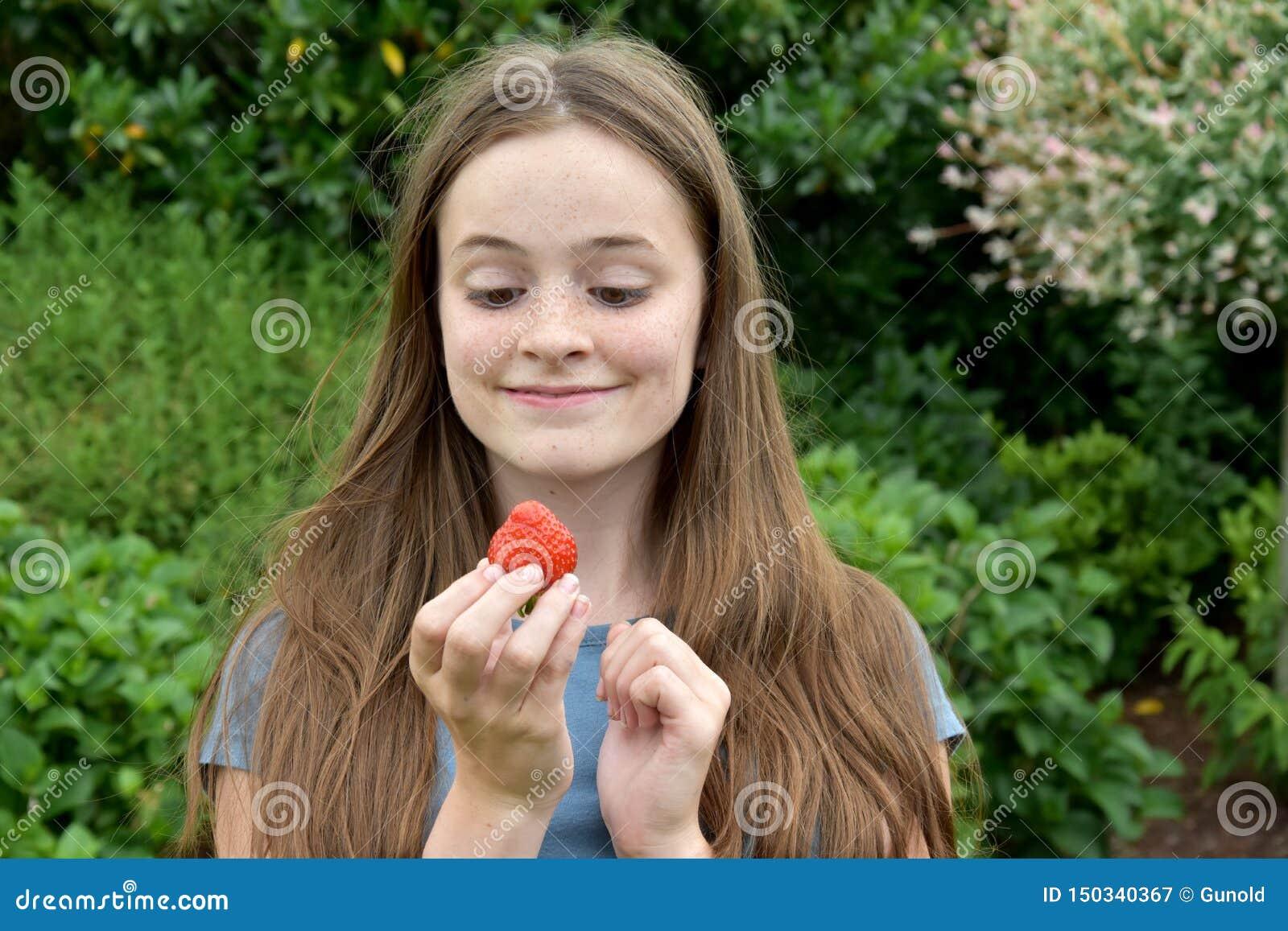 Девочка-подросток есть клубнику