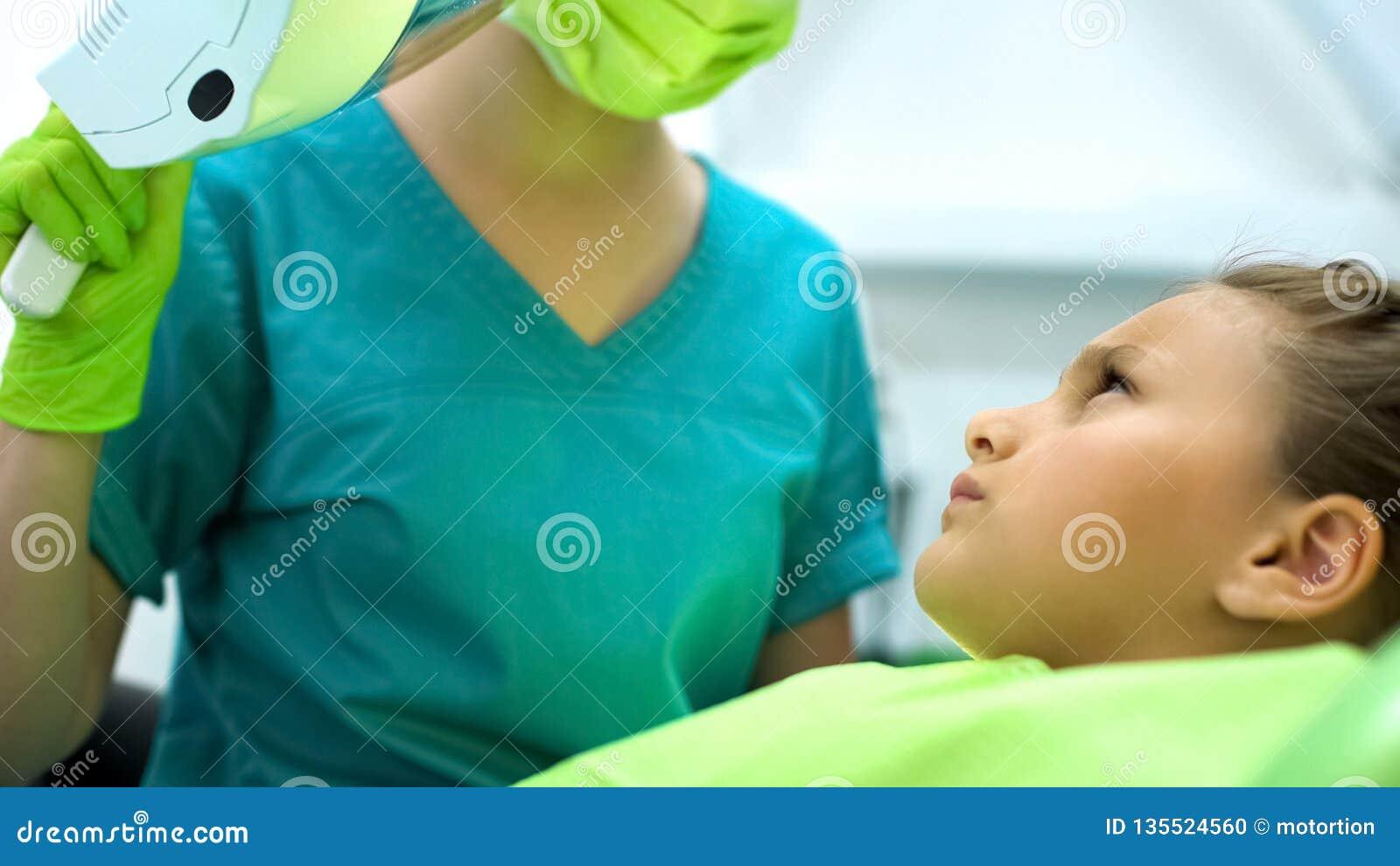 Девочка-подросток смотря педиатрический дантиста, вспугнутый сверлить, удаление костоеды