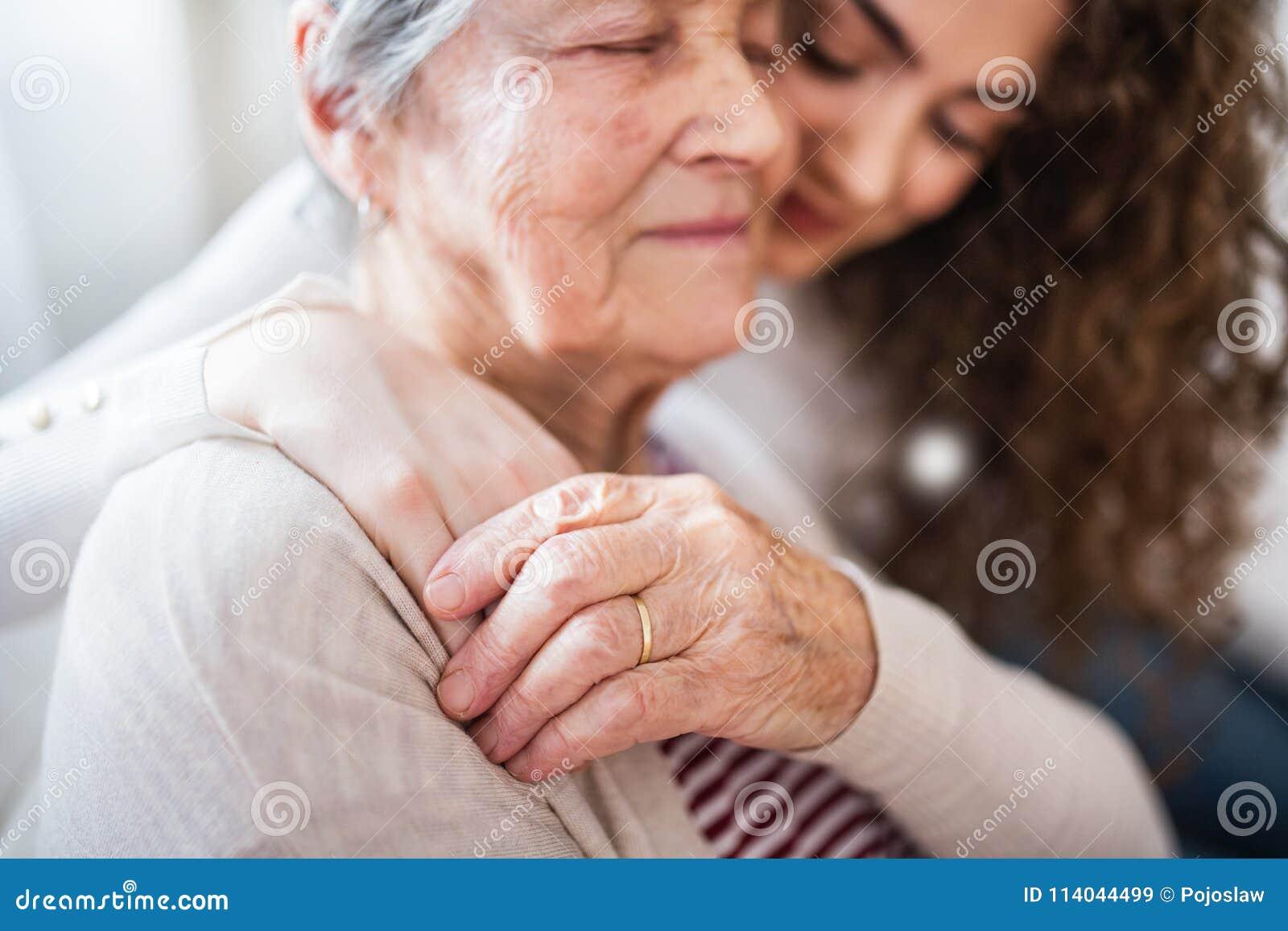 Девочка-подросток с бабушкой дома, обнимающ