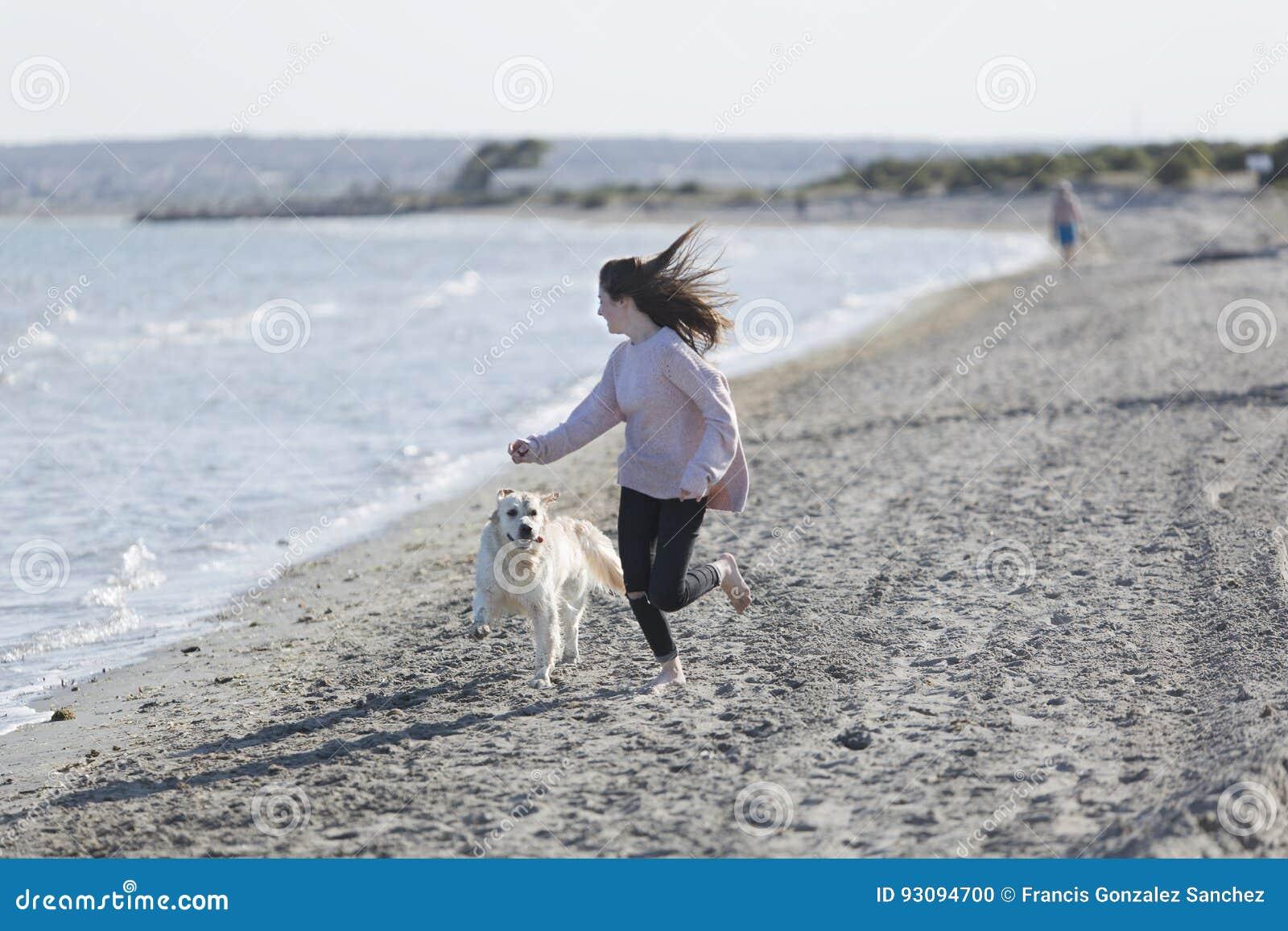Девочка-подросток играя с ее собакой на пляже
