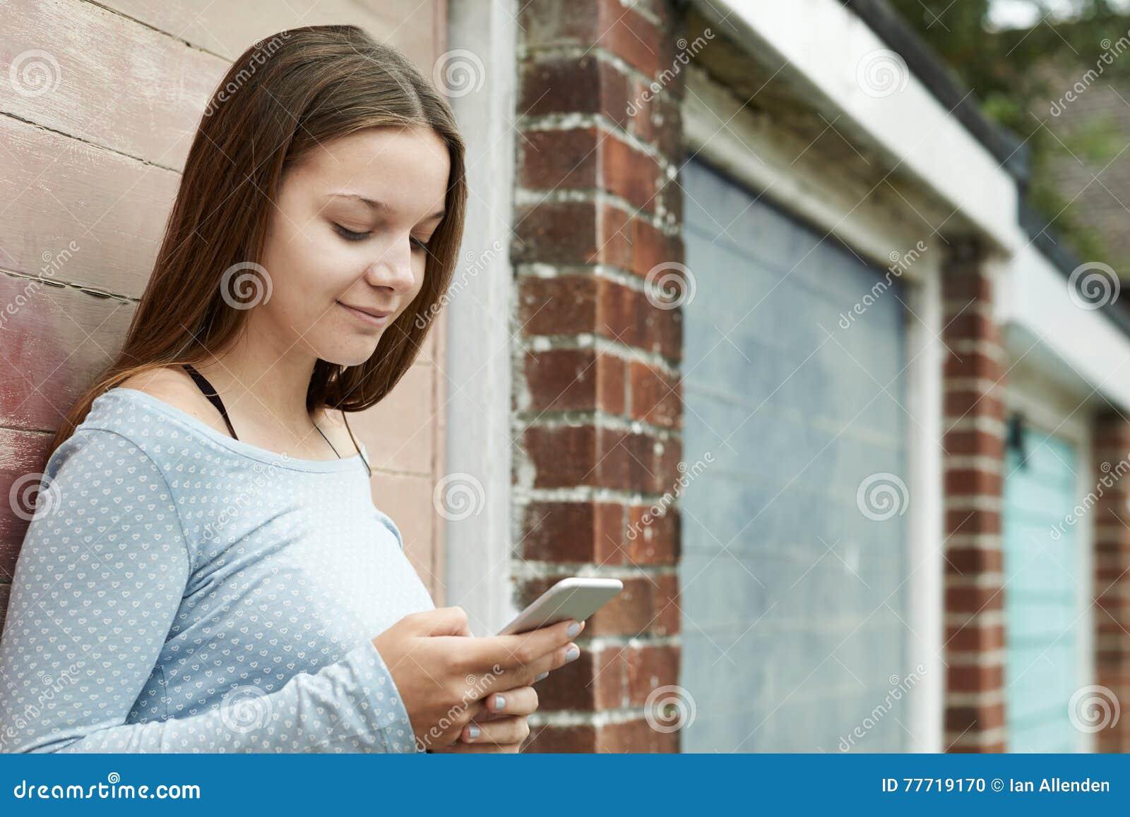 Девочка-подросток отправляя СМС на мобильном телефоне в городских условиях