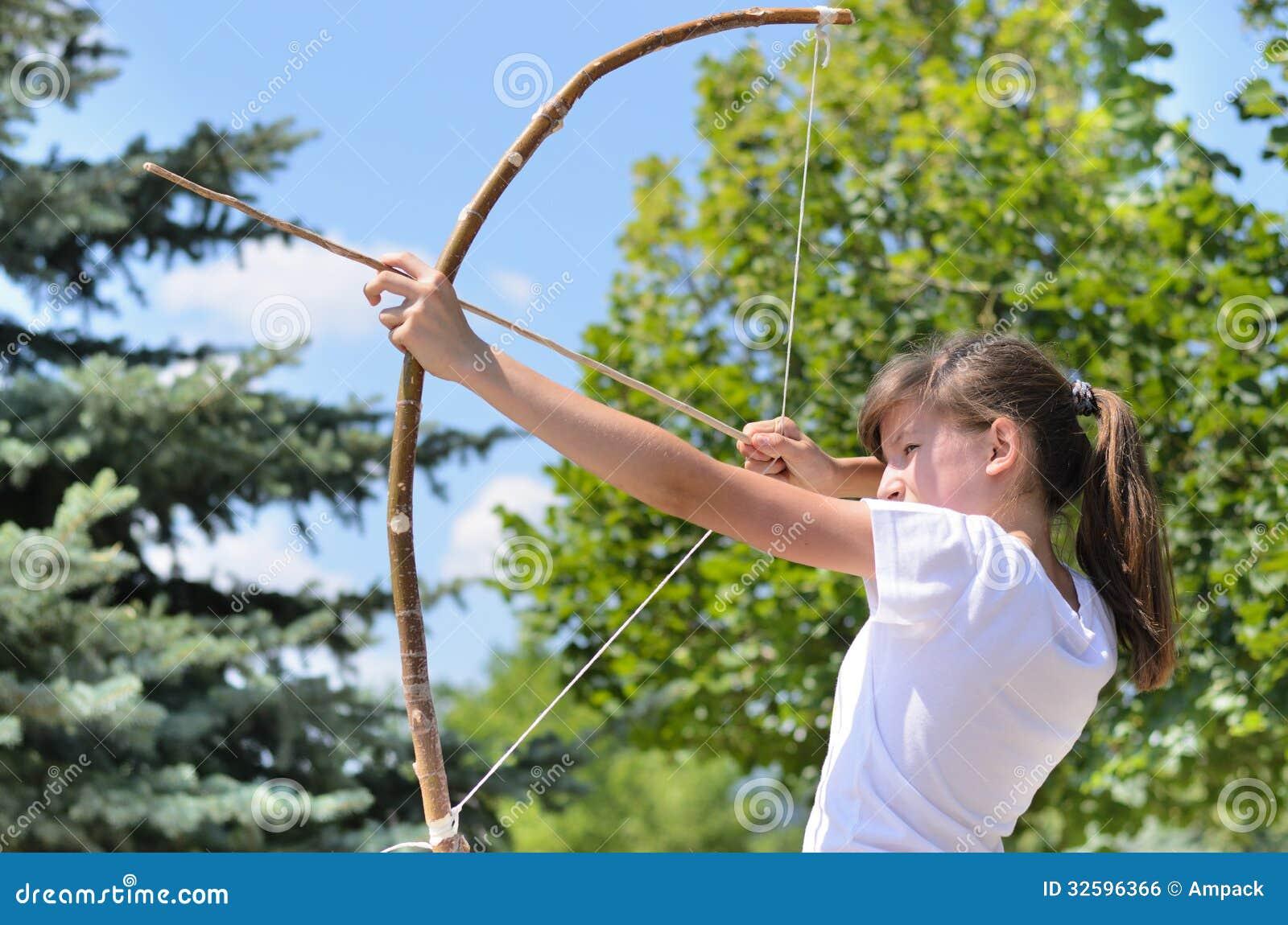 Девочка-подросток принимая цель с луком и стрелы
