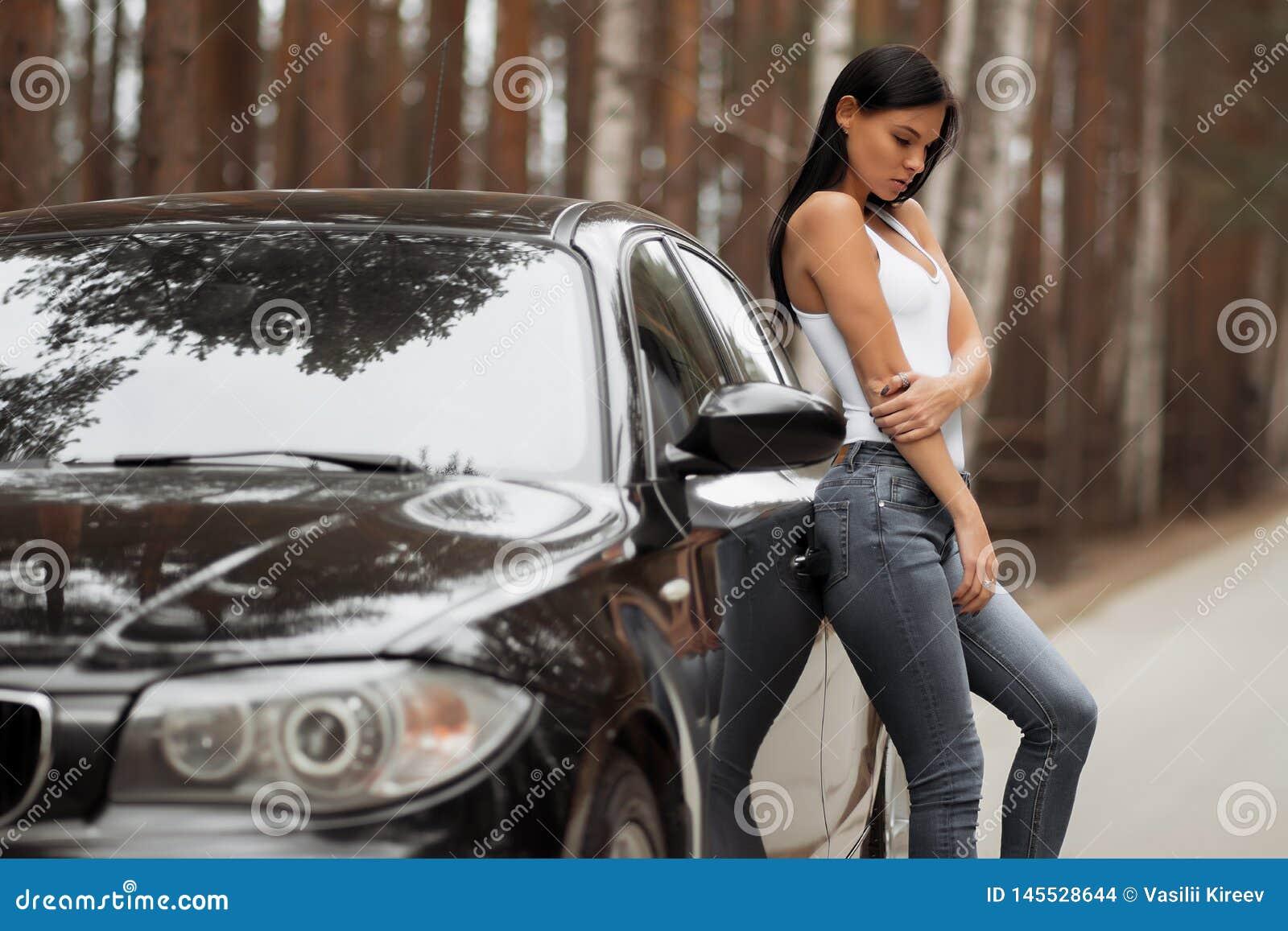 Девушка брюнета положенная против автомобиля