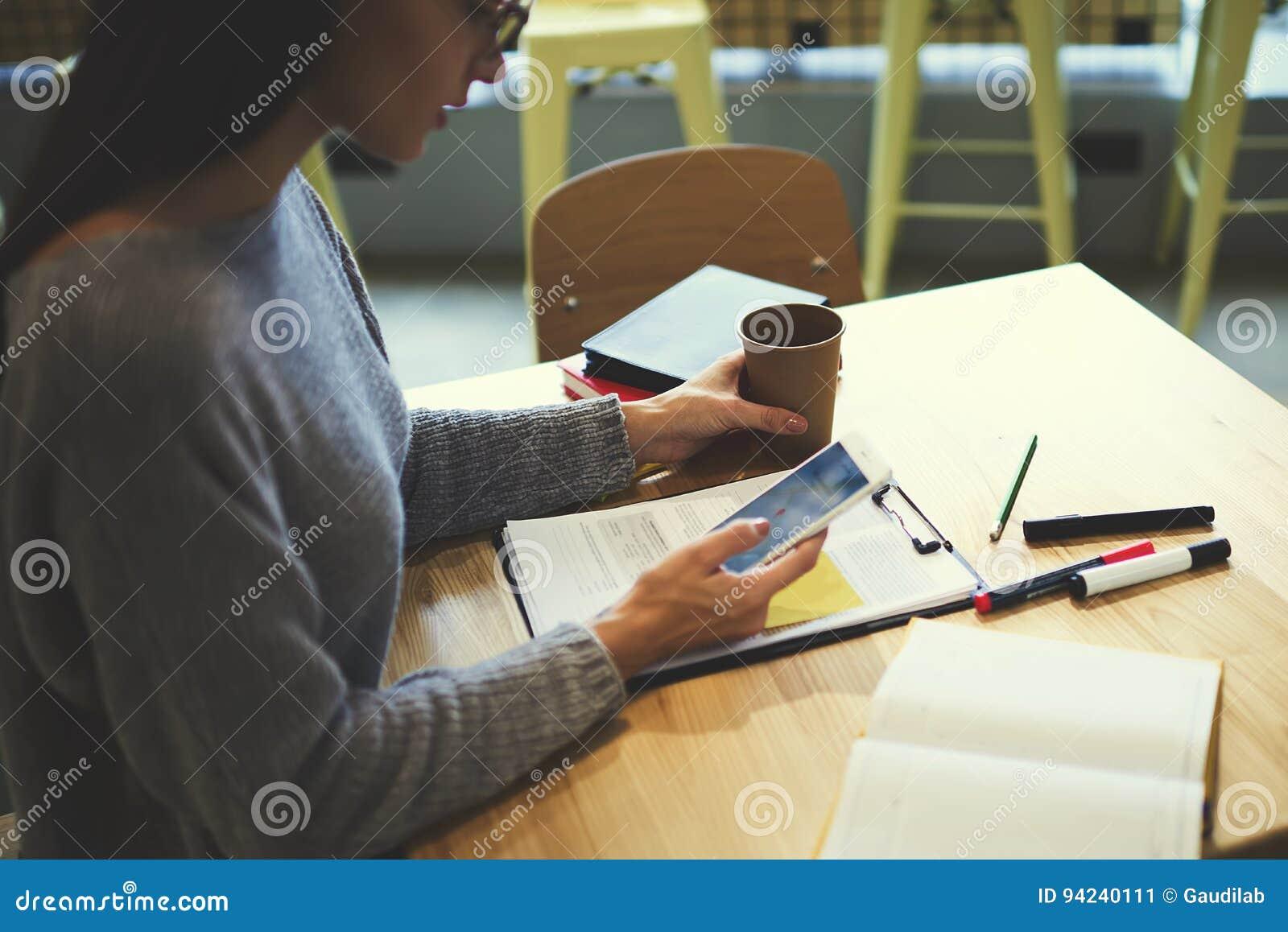 Девушка брюнет в стеклах выполняет ежедневную работу через smartphone соединенный к лучшему другу беспроволочного интернета ждать