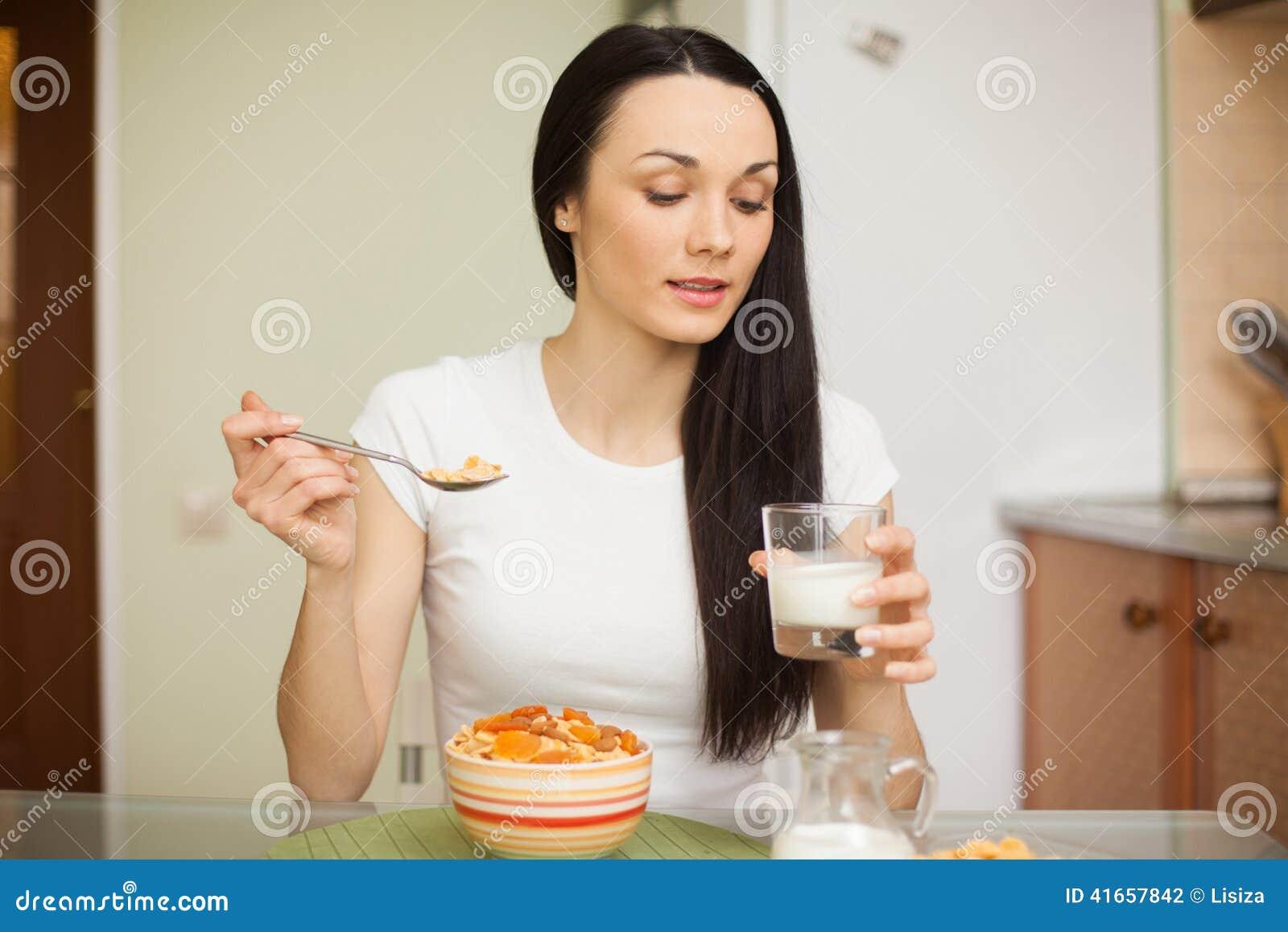Девушка брюнет есть завтрак с молоком в кухне