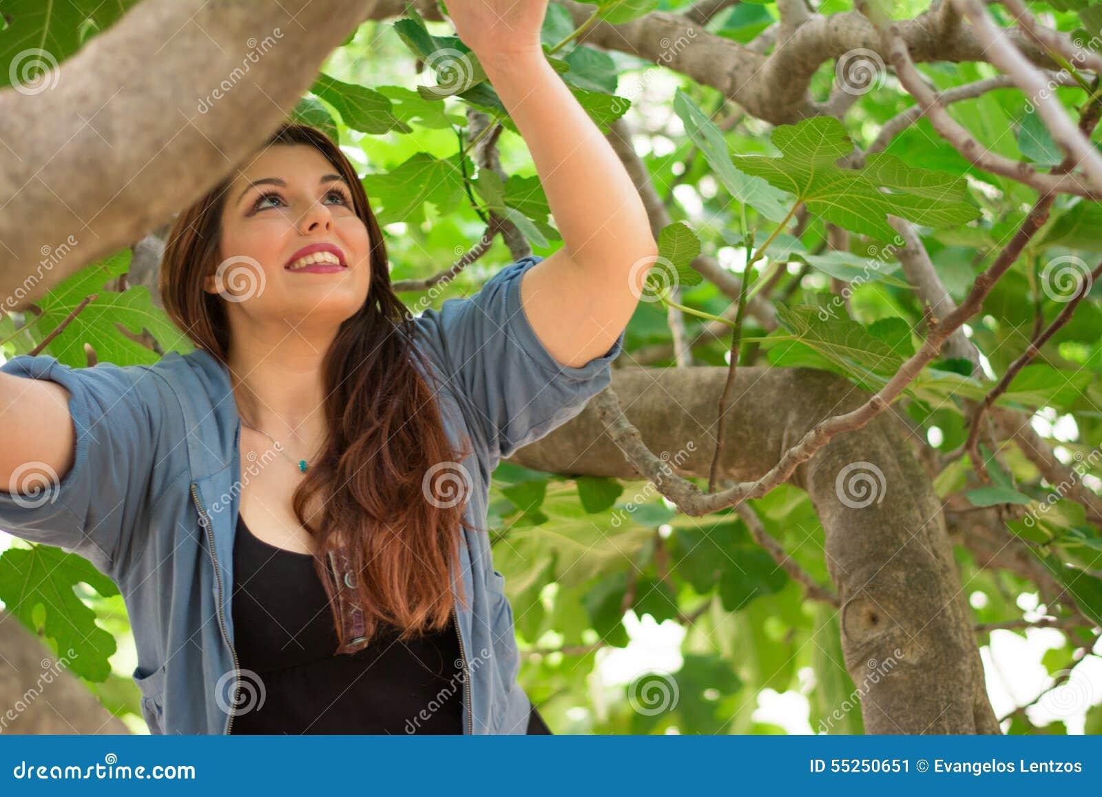 Девушка взбираясь на смоковнице