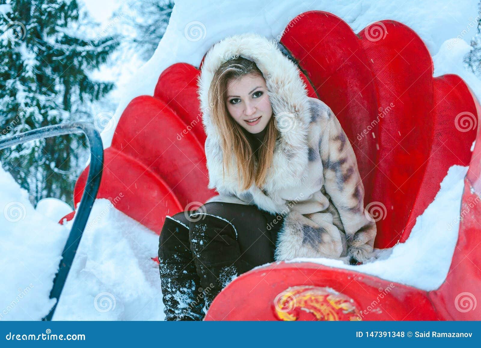 Девушка в бежевых коротких пальто и клобуке сидит на красном carousel