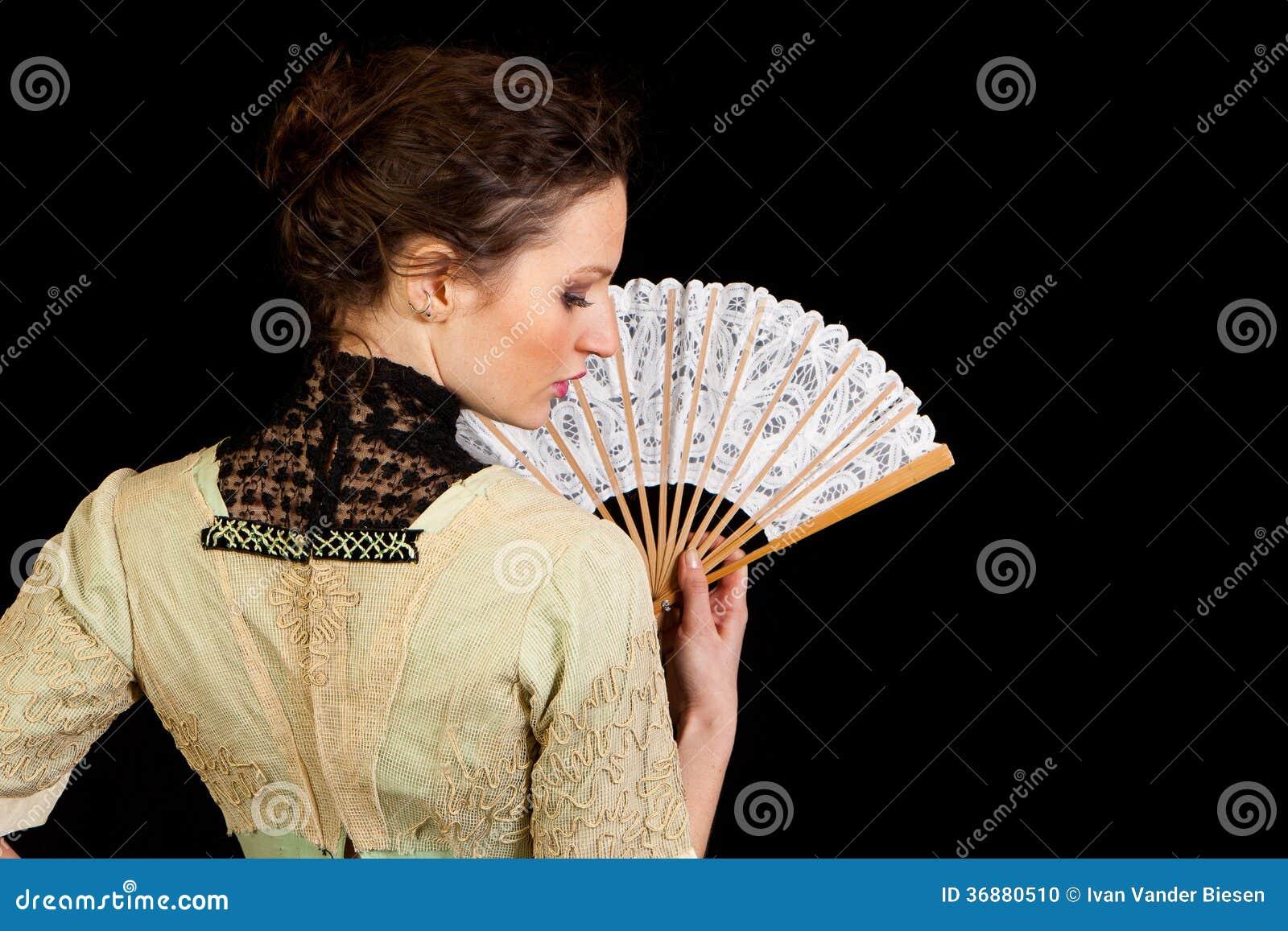 Девушка в викторианском платье при вентилятор увиденный от задней части