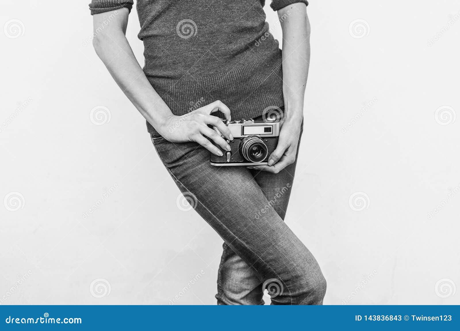 Девушка в джинсах держит старую винтажную камеру фильма на бедрах