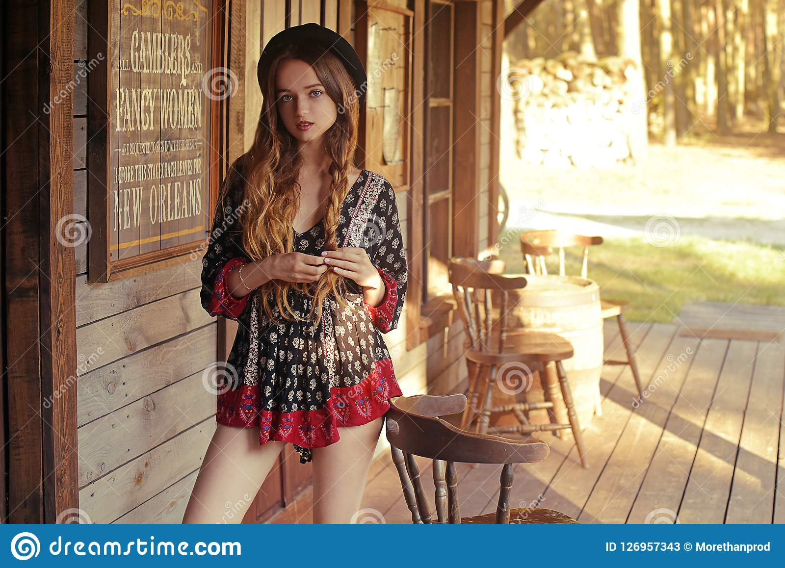 Девушка в Диких Западах, в западном доме Девушка в шляпе с длинными cerly волосами Красивая милая девушка в черной шляпе Неимовер