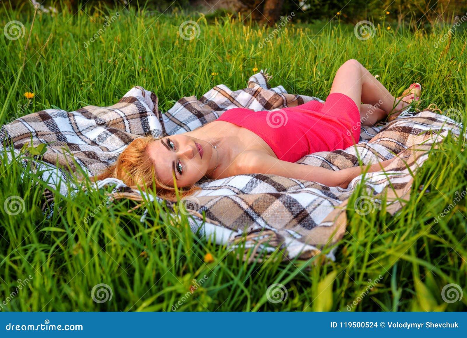 Девушка в красном платье лежа на траве
